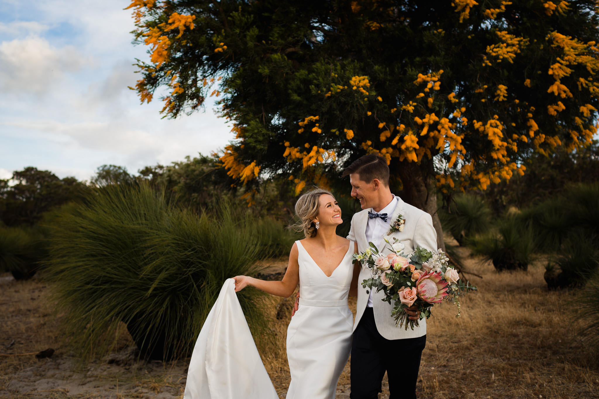 Bride holding dress and walking with husband holding native protea bouquet in front of Australia Christmas tree with yellow flowers at Solitaire Homestead