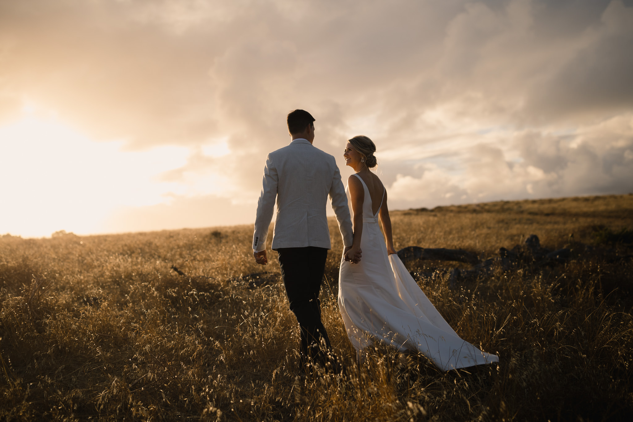 Bride and groom walking through field of golden grass at sunset in Yallingup near Margaret River