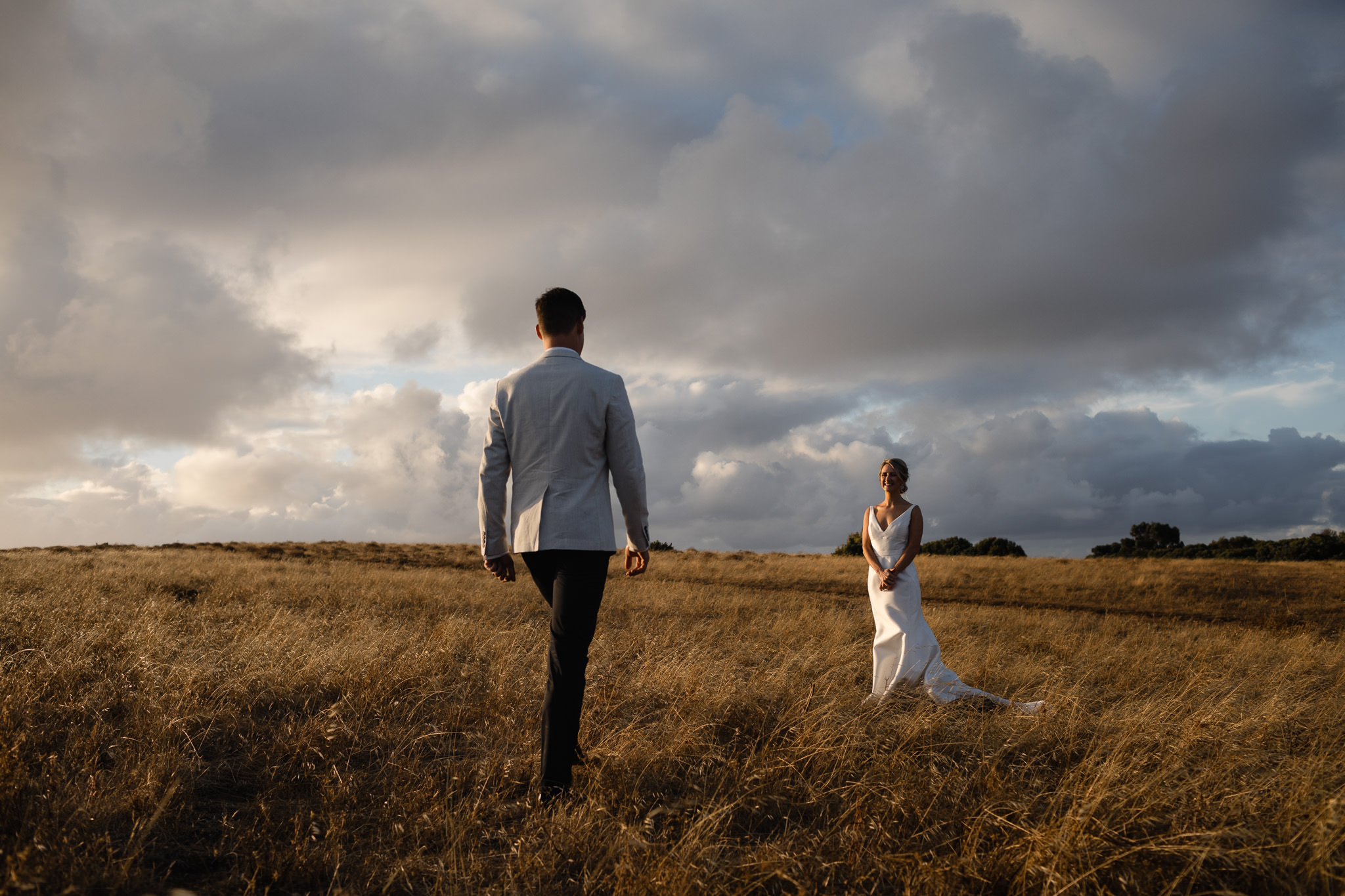Bride standing in field of golden grass at sunset while groom walks towards her
