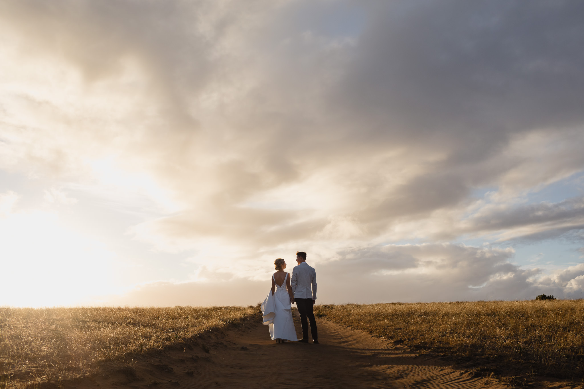 Bride and groom standing on red dirt road between golden fields or grass at Solitaire Homestead wedding