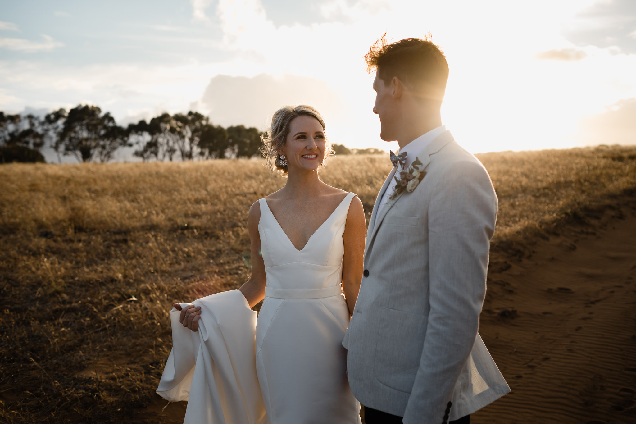 Bride and groom smiling and looking at each other lovingly at sunset with sun flare