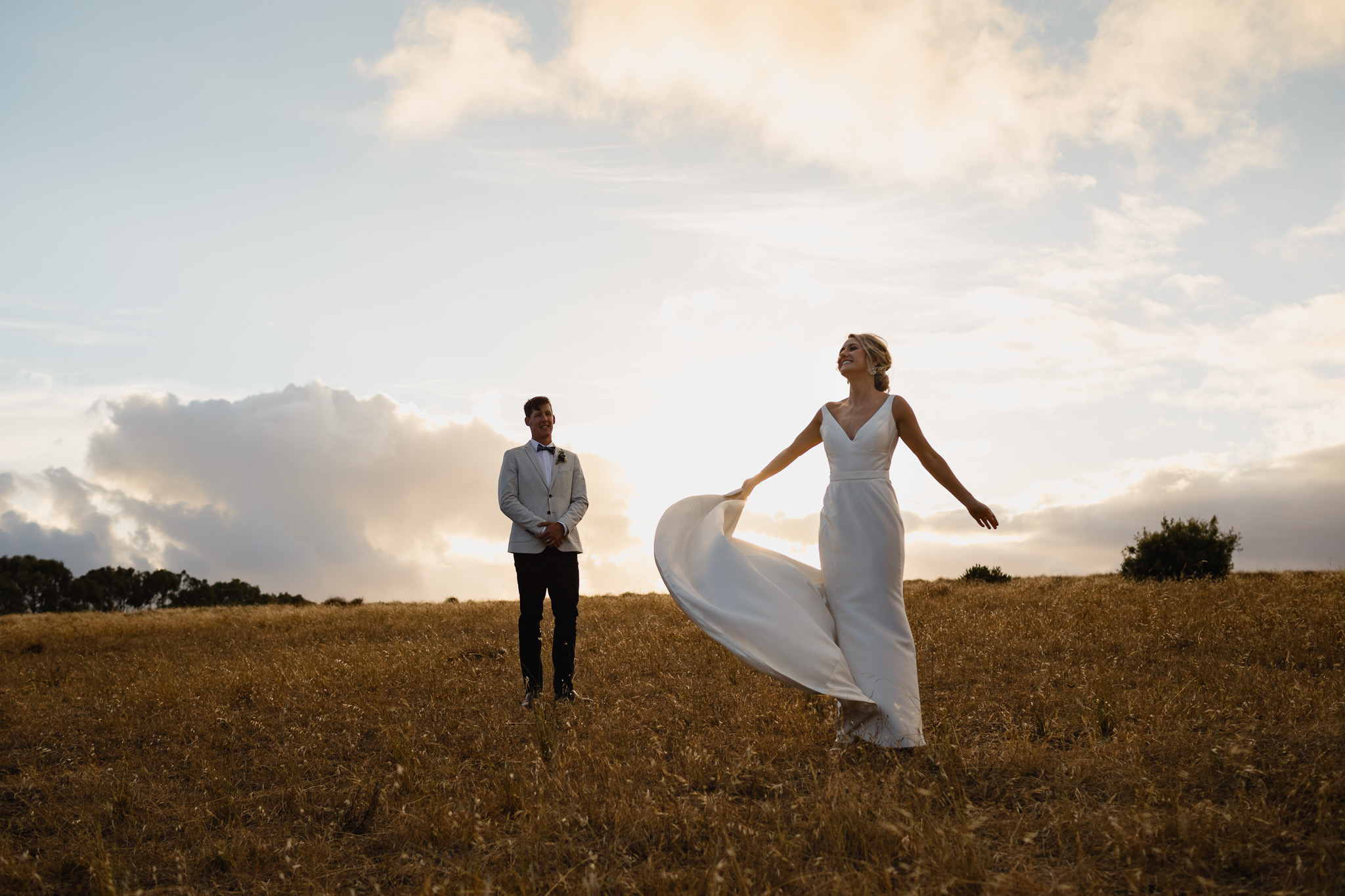 Bride holding dress and spinning around in a field at outdoor wedding in Yallingup