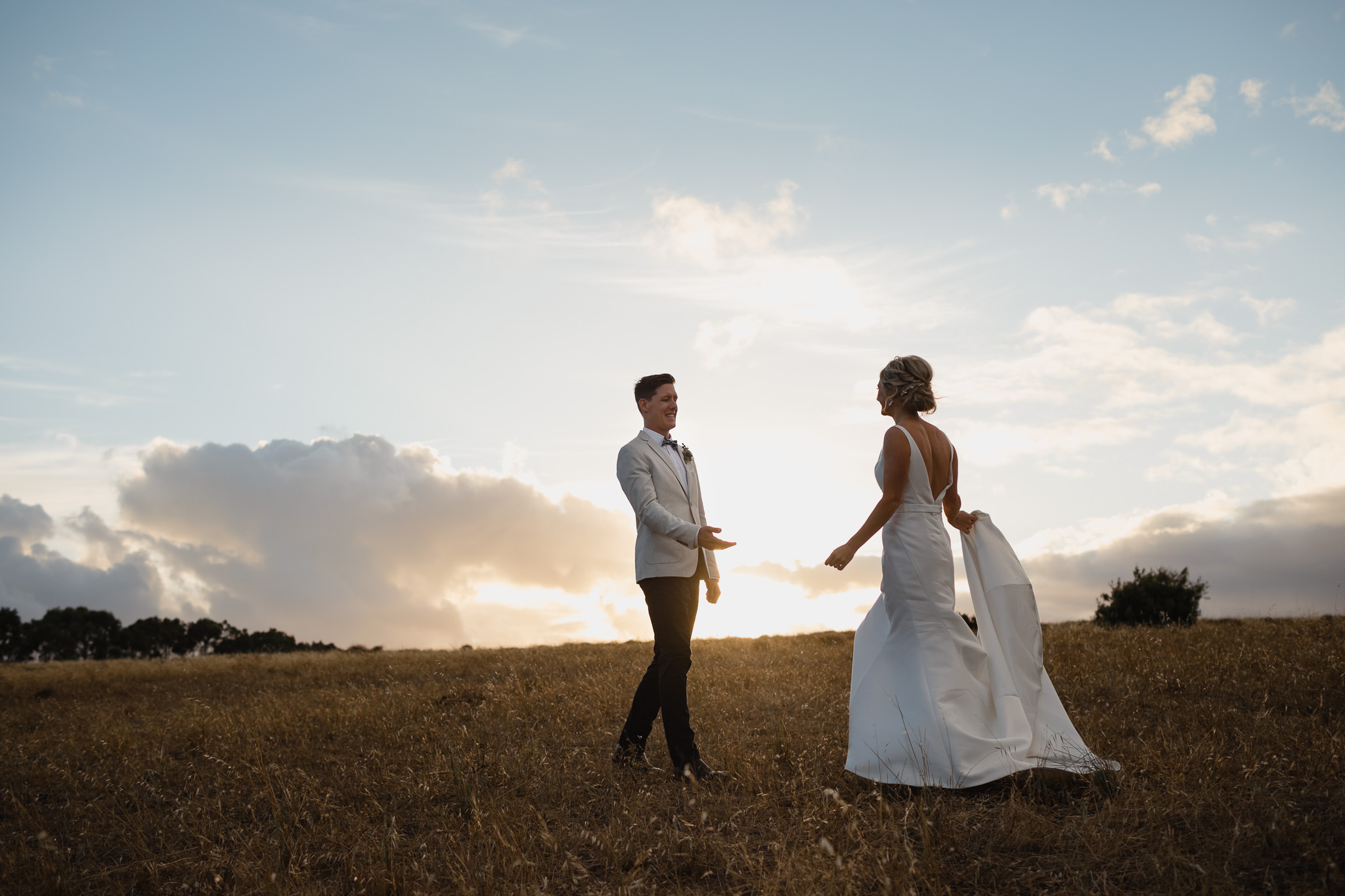 Groom holding outstretched hand towards bride as they walk towards each other at a farm wedding at sunset in Margaret River
