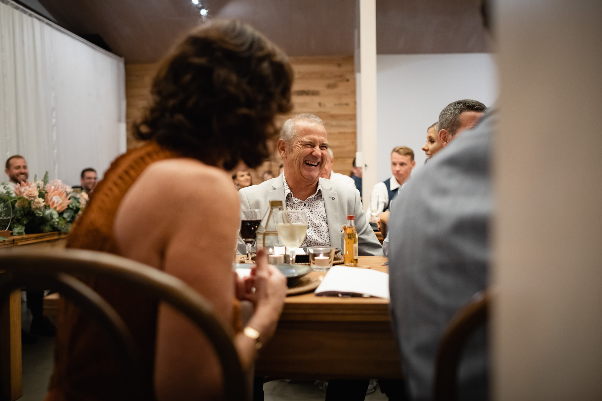 Irish father of the bride laughing during wedding speeches with small bottle of whiskey on the table