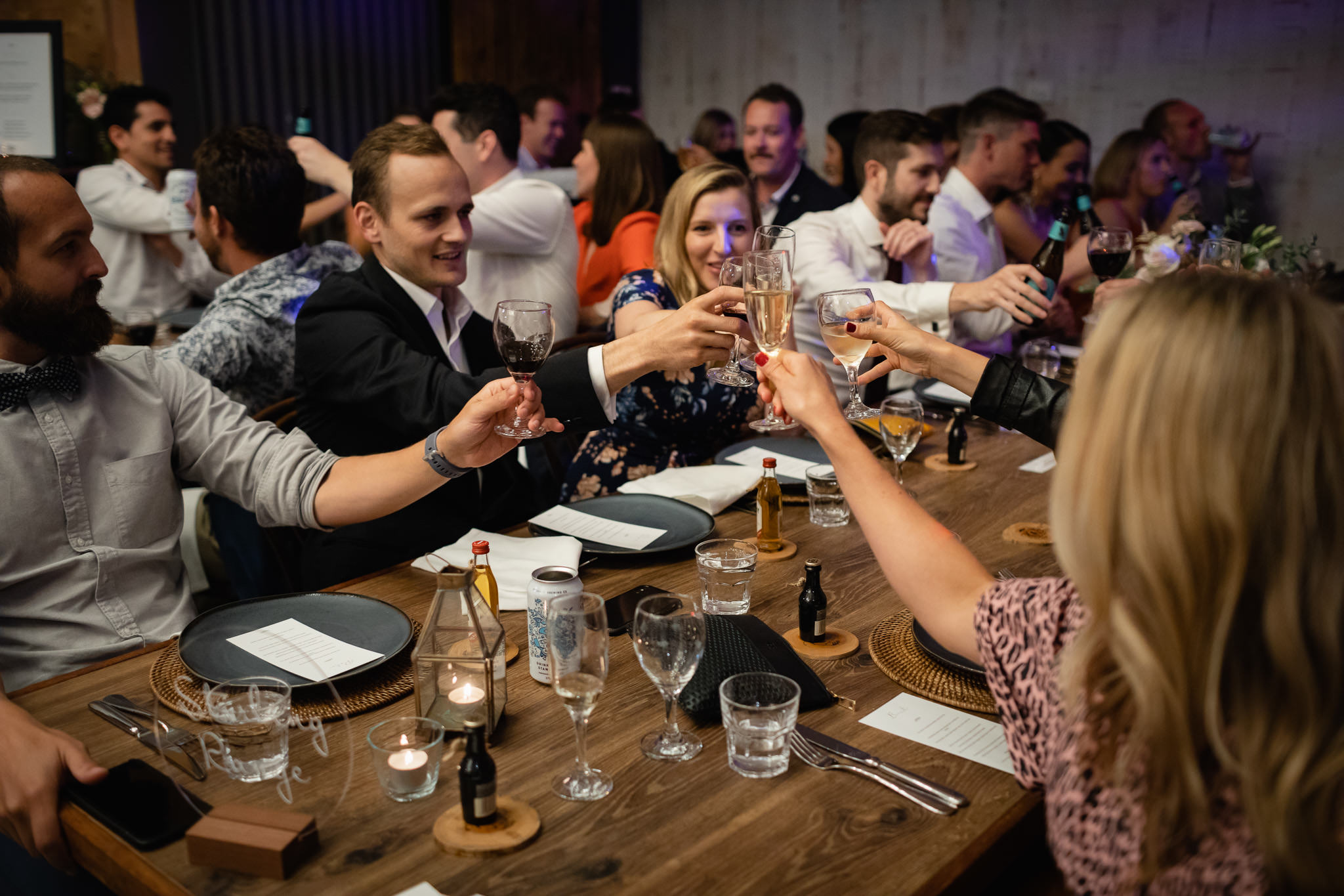 Guests clinking glasses during wedding toast at wedding reception