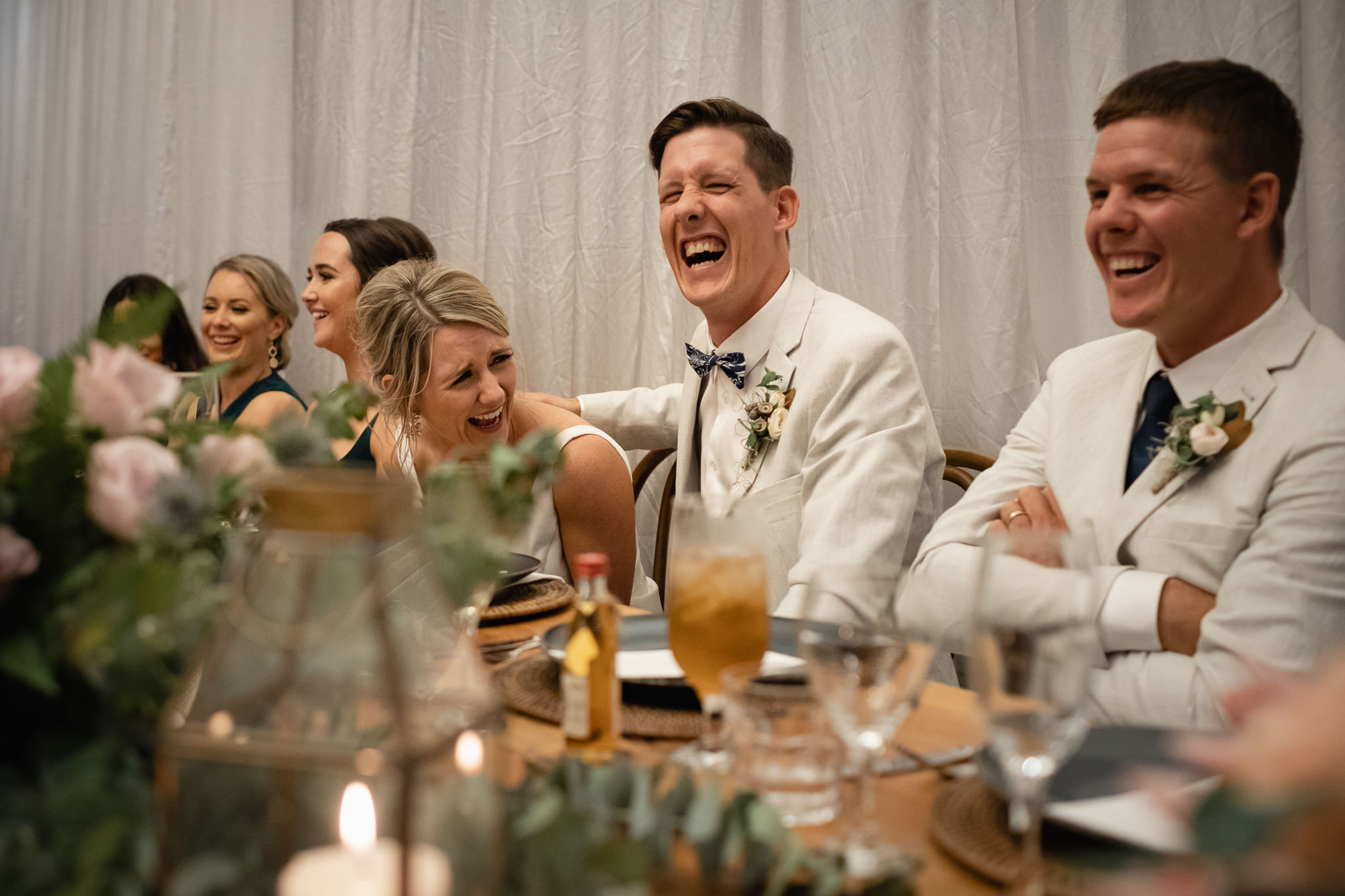 Bride and groom laughing during hilarious wedding speeches