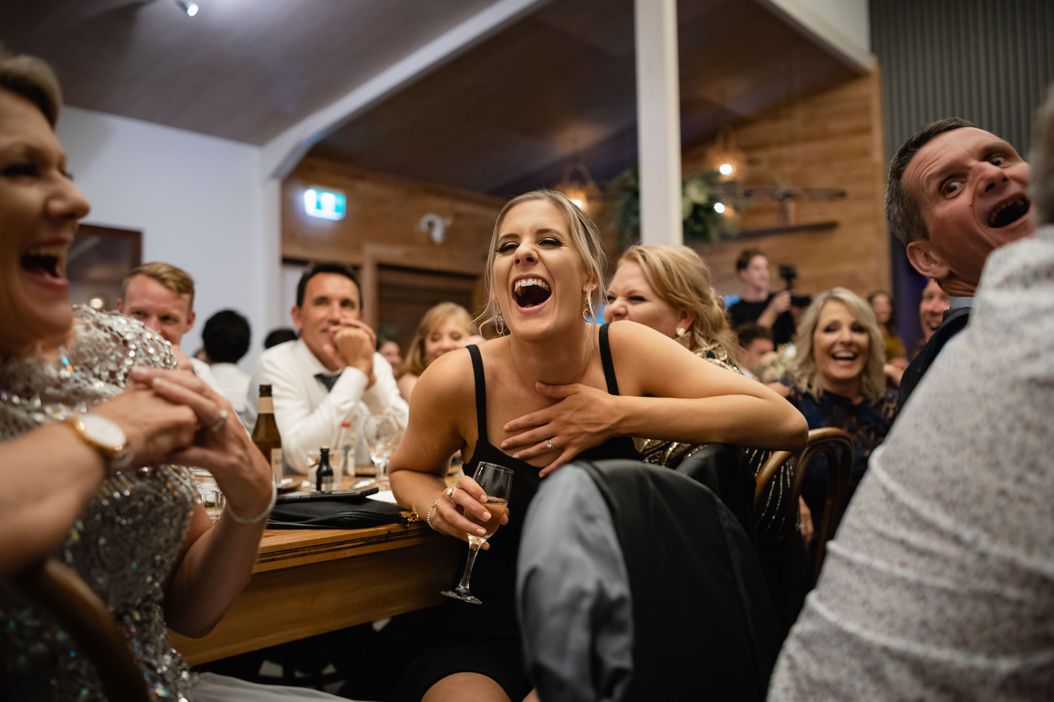 Wedding guests laughing during funny wedding speeches at wedding reception