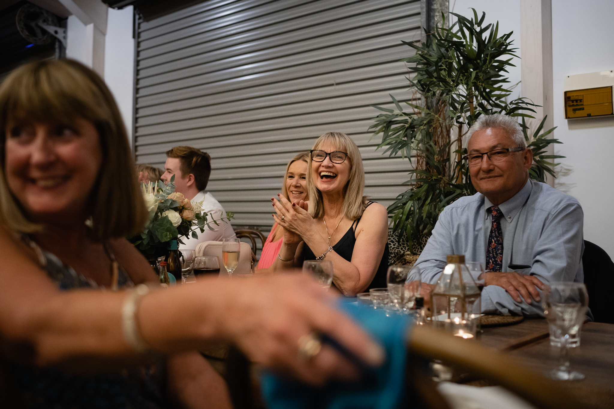 Family friend laughing and clapping during wedding speeches