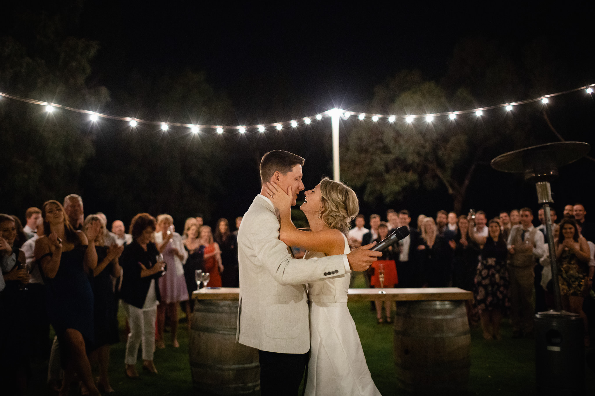 Bride and groom embracing under festoon lights at outdoor farm wedding at Solitaire Homestead in front of all of their guests