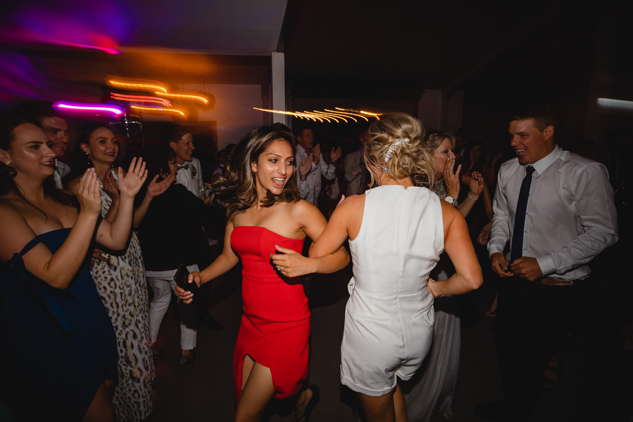 Girl in red dress dances with bride at wedding reception with light streaks in background