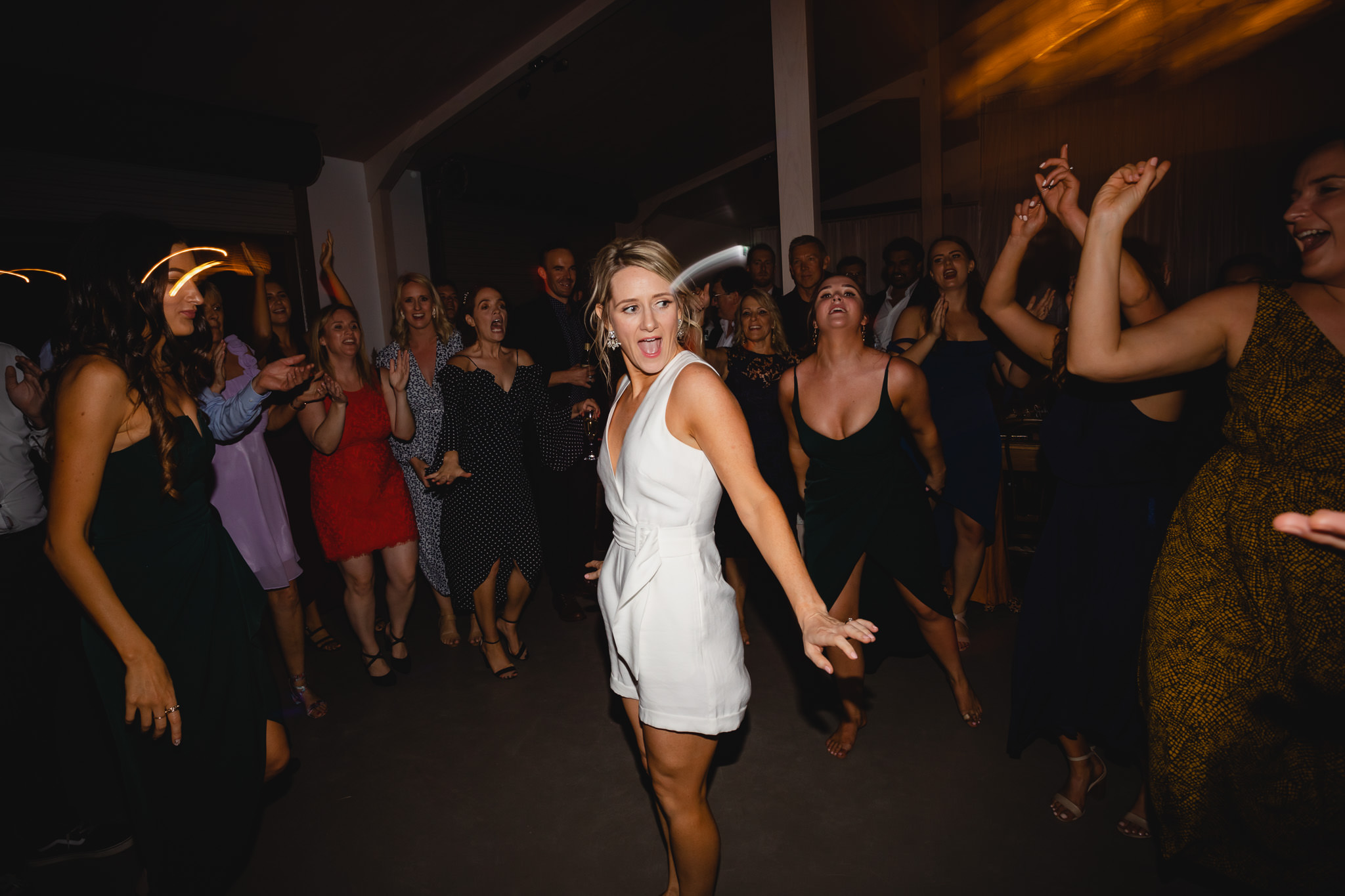 bride throwing dance moves in white wedding jumpsuit at wedding reception