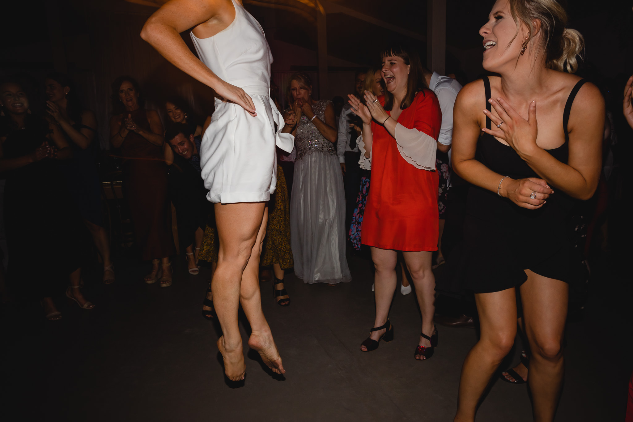 Bride in white wedding jumpsuit jumping in air doing Irish dancing at wedding