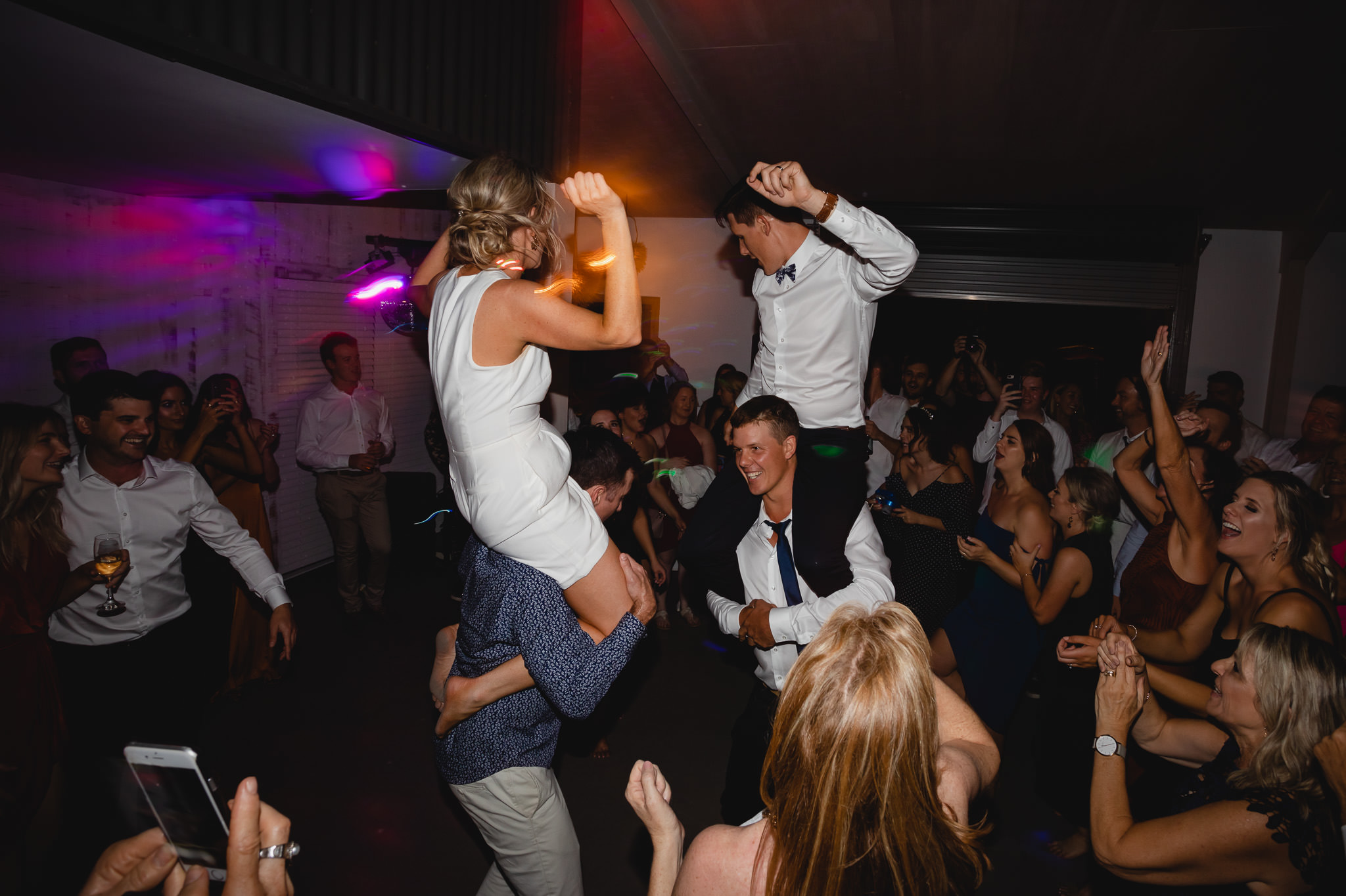Bride and groom being chaired on friend's shoulders on dance floor at Solitaire Homestead wedding reception