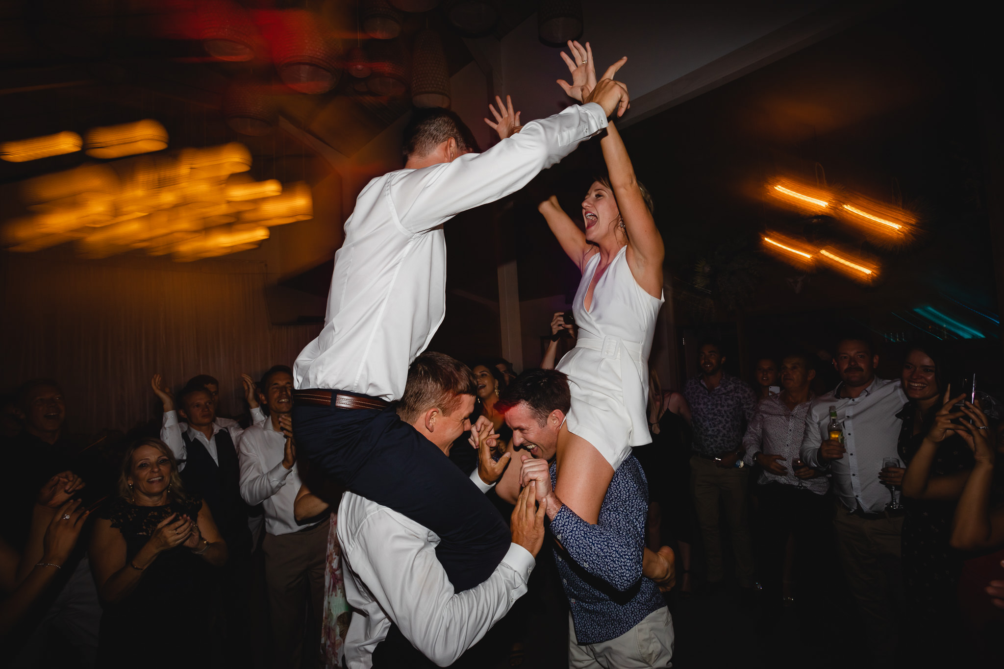 Bride and groom holding hands and being chaired on friend's shoulders on dance floor at Solitaire Homestead