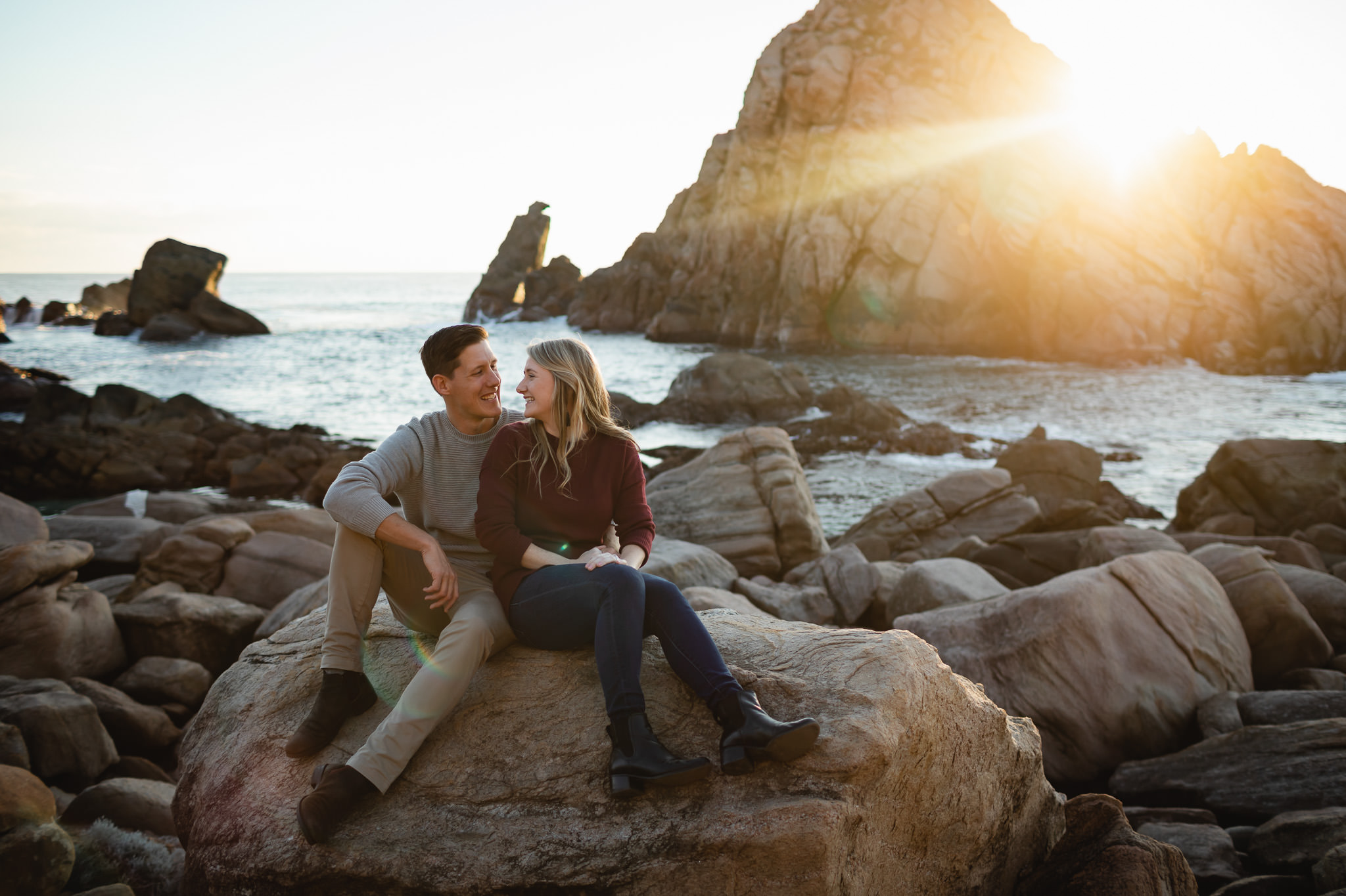 Couple sitting on rocks in front of Sugarloaf Rock near Yallingup at sunset with sun flare