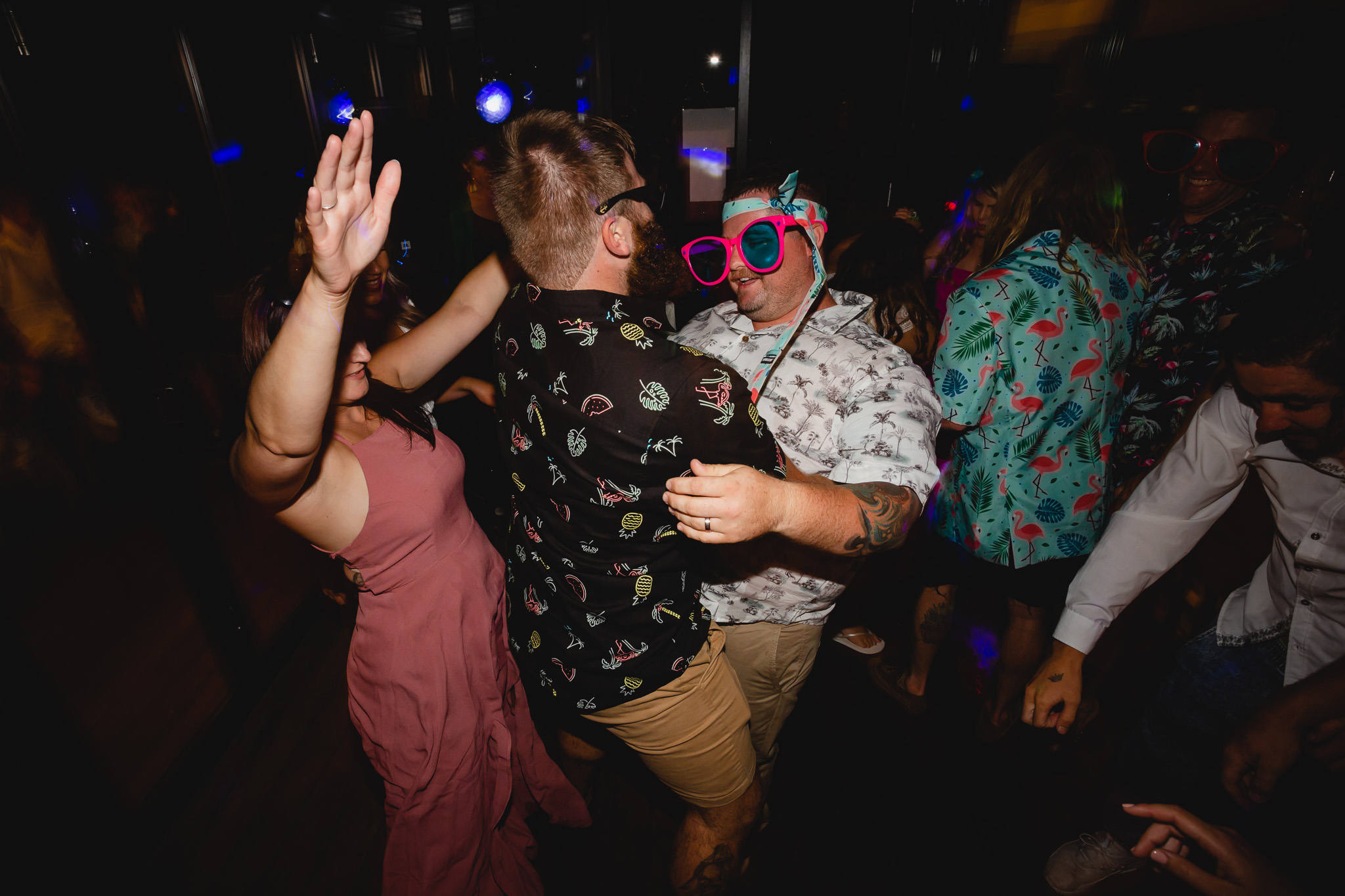 Groom wearing Hawaiian shirt and crazy pink photo booth glasses dancing at Bunkers Beach House at his wedding