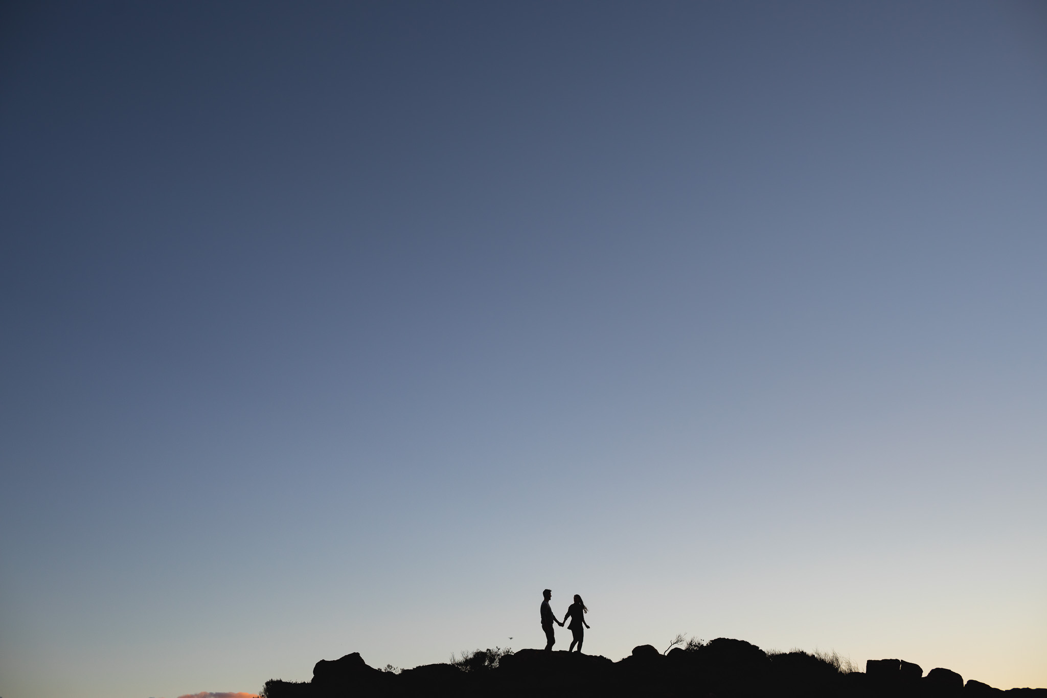 Tiny couple walking along rocks at Sugarloaf Rock with huge blue sky framing them with negative space