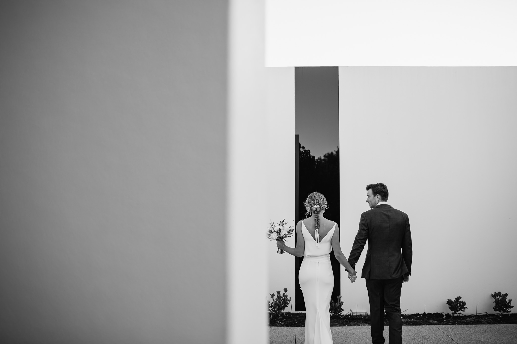 black and white photo of bride and groom outside modern architecture home with minimalist design