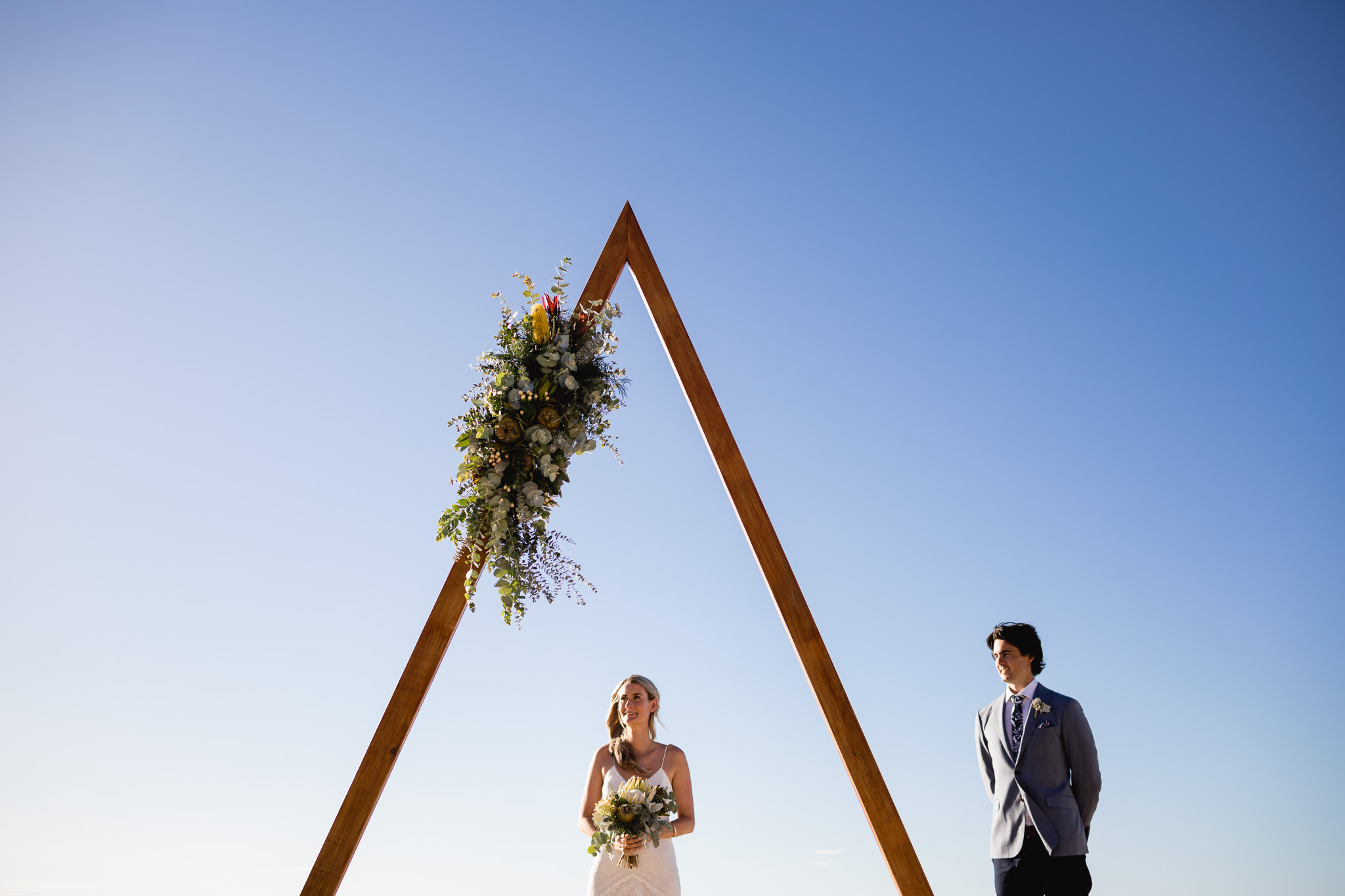 Bride and groom under giant triangle arbour with native flowers at Injidup Beach