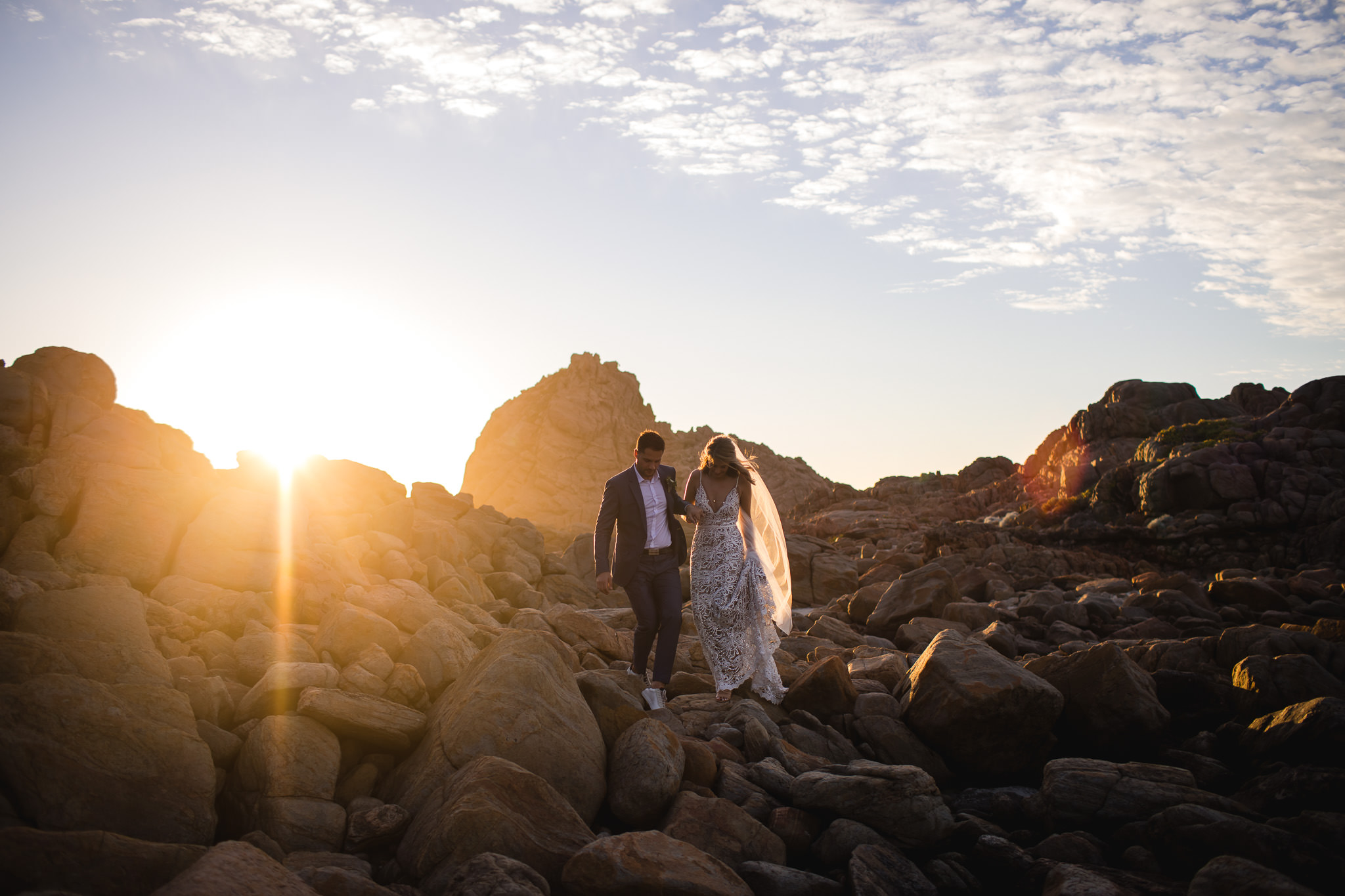Groom wearing white sneakers with his grey suit and bride in Made by Love wedding dress walking along rocks landscape at sunset