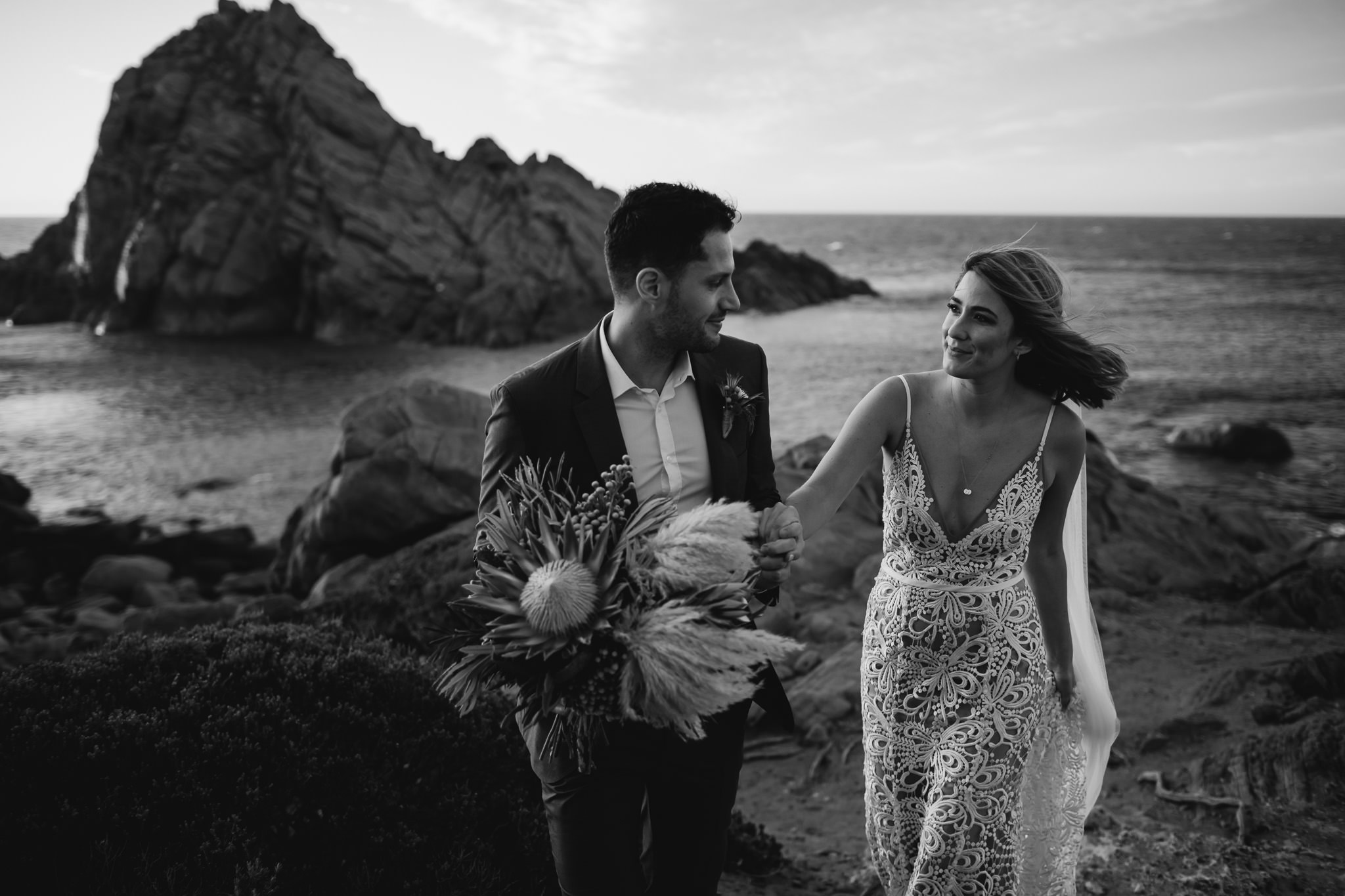 Black and white photo of bride and groom walking at along rocky coastal path. Bride is wearing Made with Love dress and groom is holding protea and pampas grass bouquet