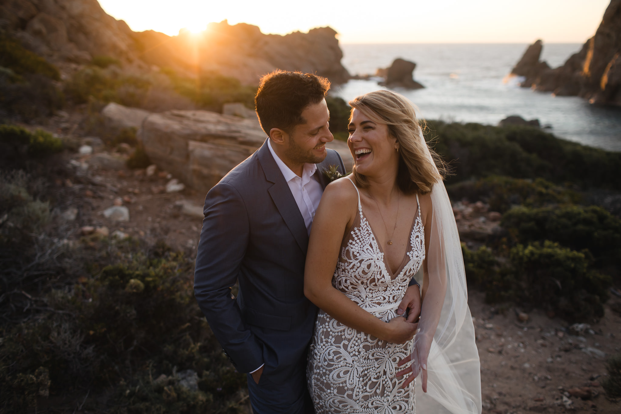 Groom hugging bride as she lens back into him. Her hair is blowing in the wind and they are both laughing with a beautiful golden sunset in the background