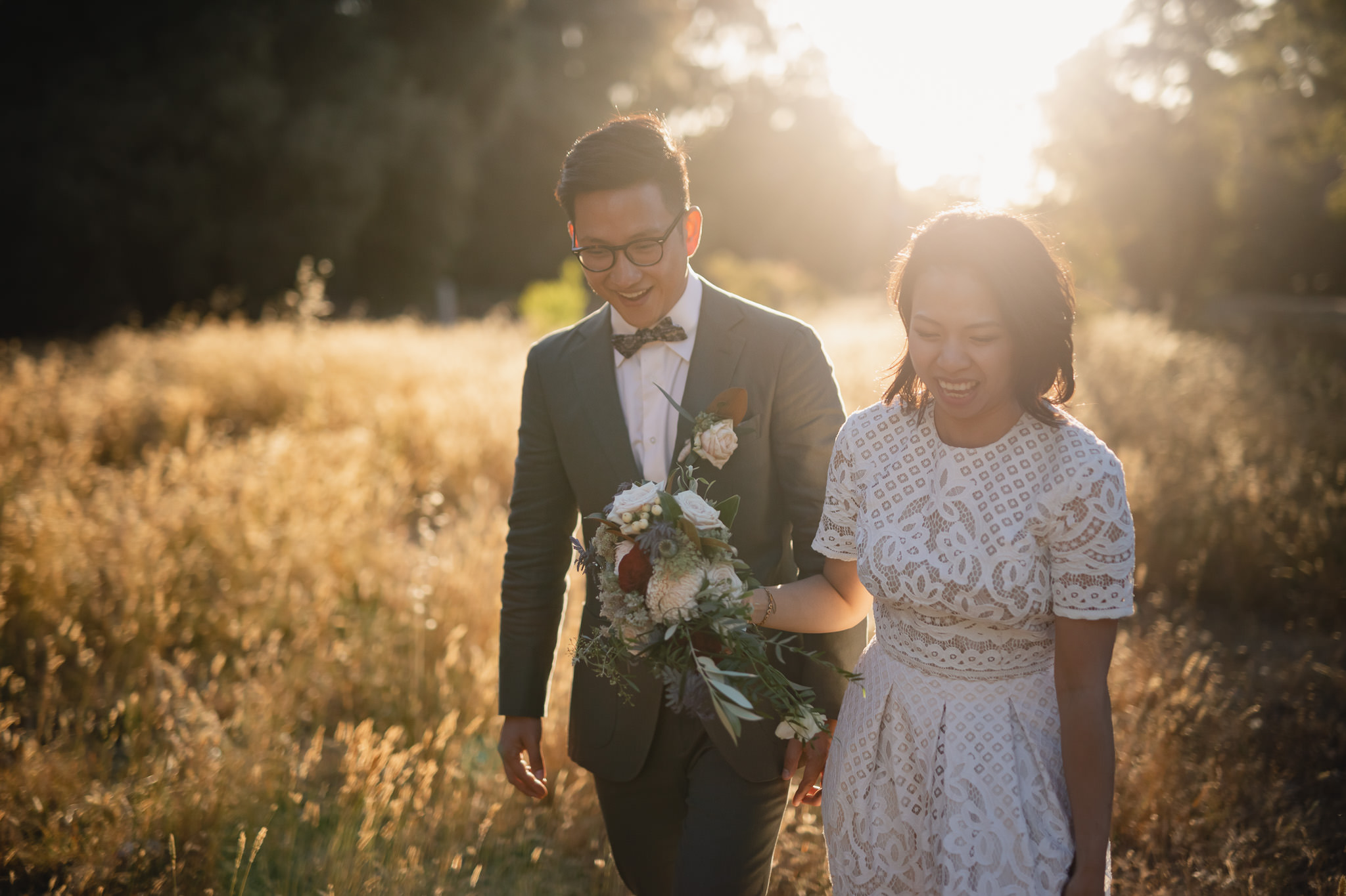 Singaporean chinese couple with vintage style walking through golden field at sunset at Karridale Cottages near Margaret River at their wedding