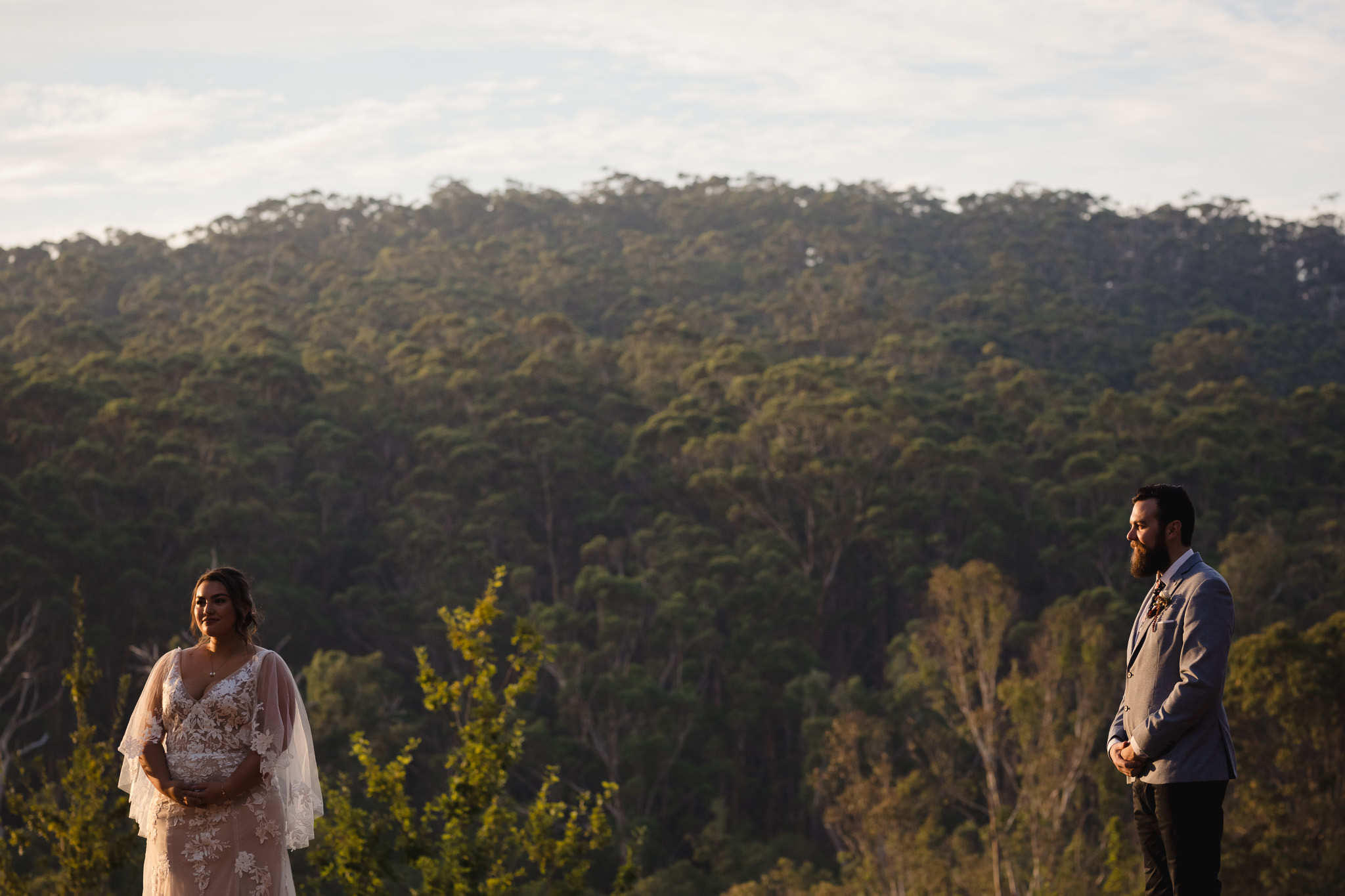 Bride and groom standing apart from each other at sunset at Stonebarn Lodge in Pemberton on their wedding day with karri forest in the background behind them