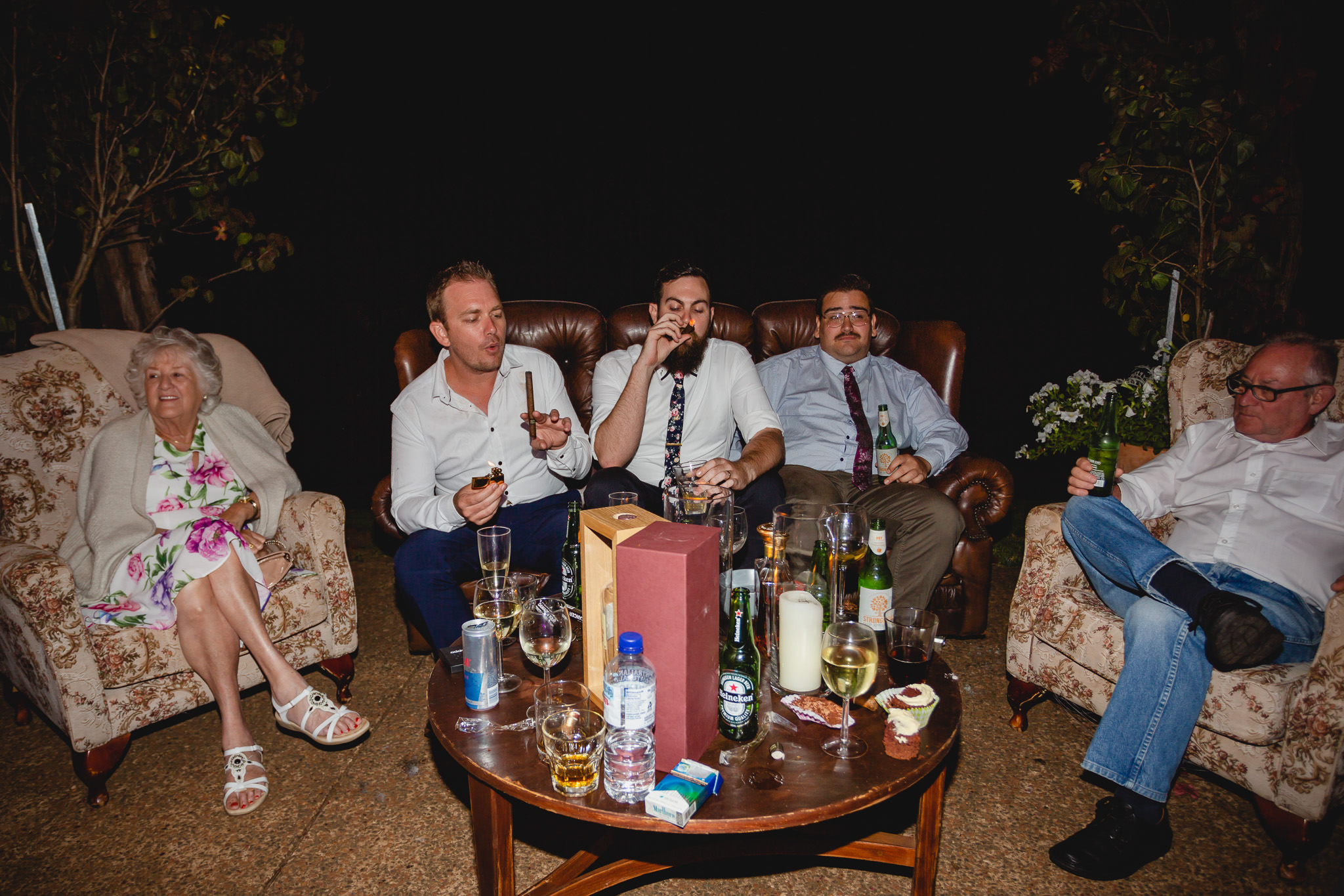 Groom and friends smoking cigars while sitting on leather couch in front of coffee table filled with drinks at Stonebarn Lodge in Pemberton at wedding reception