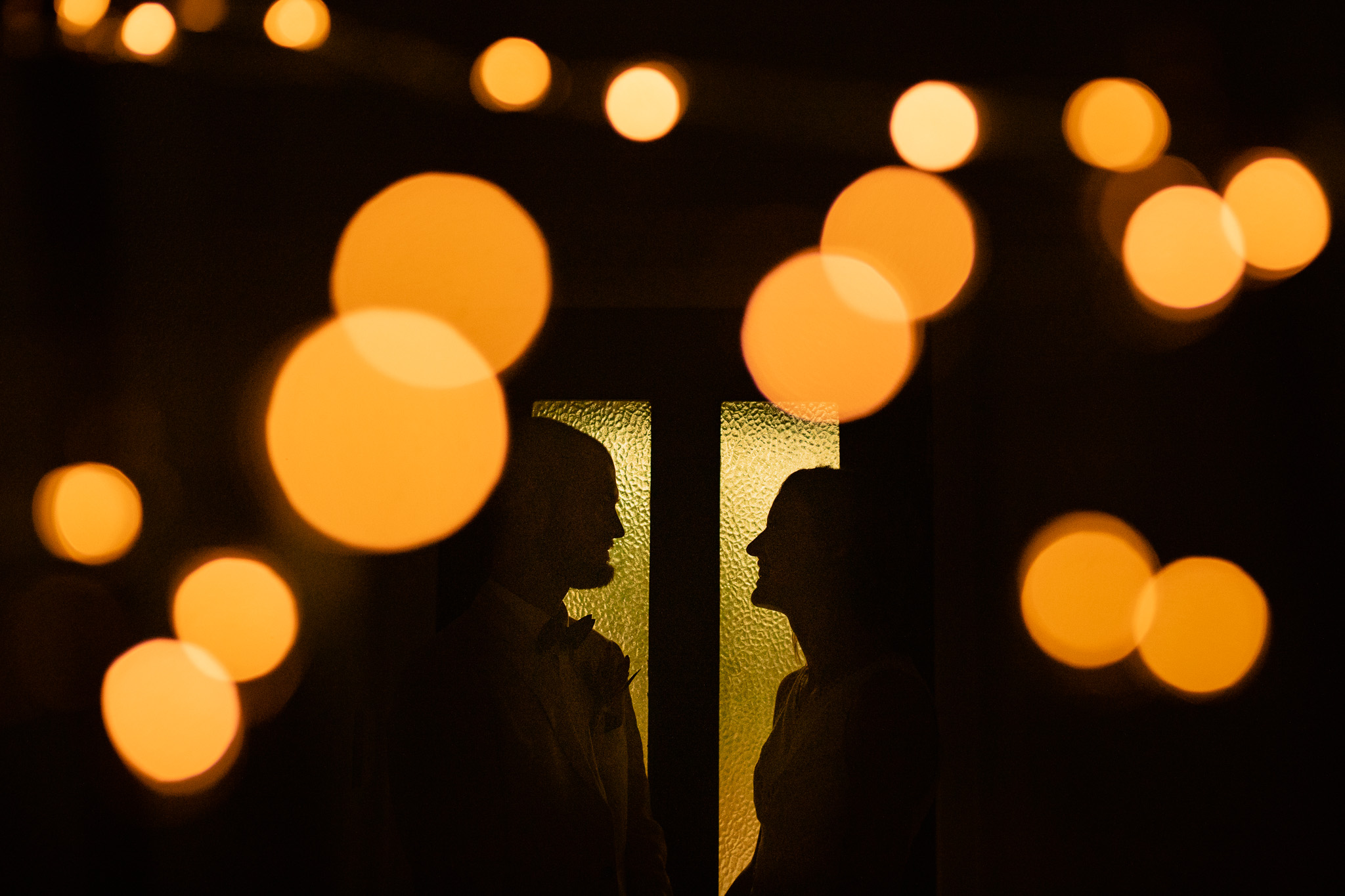 Silhouetted photo of bride and groom against green glass door with orange bokeh from fairy lights