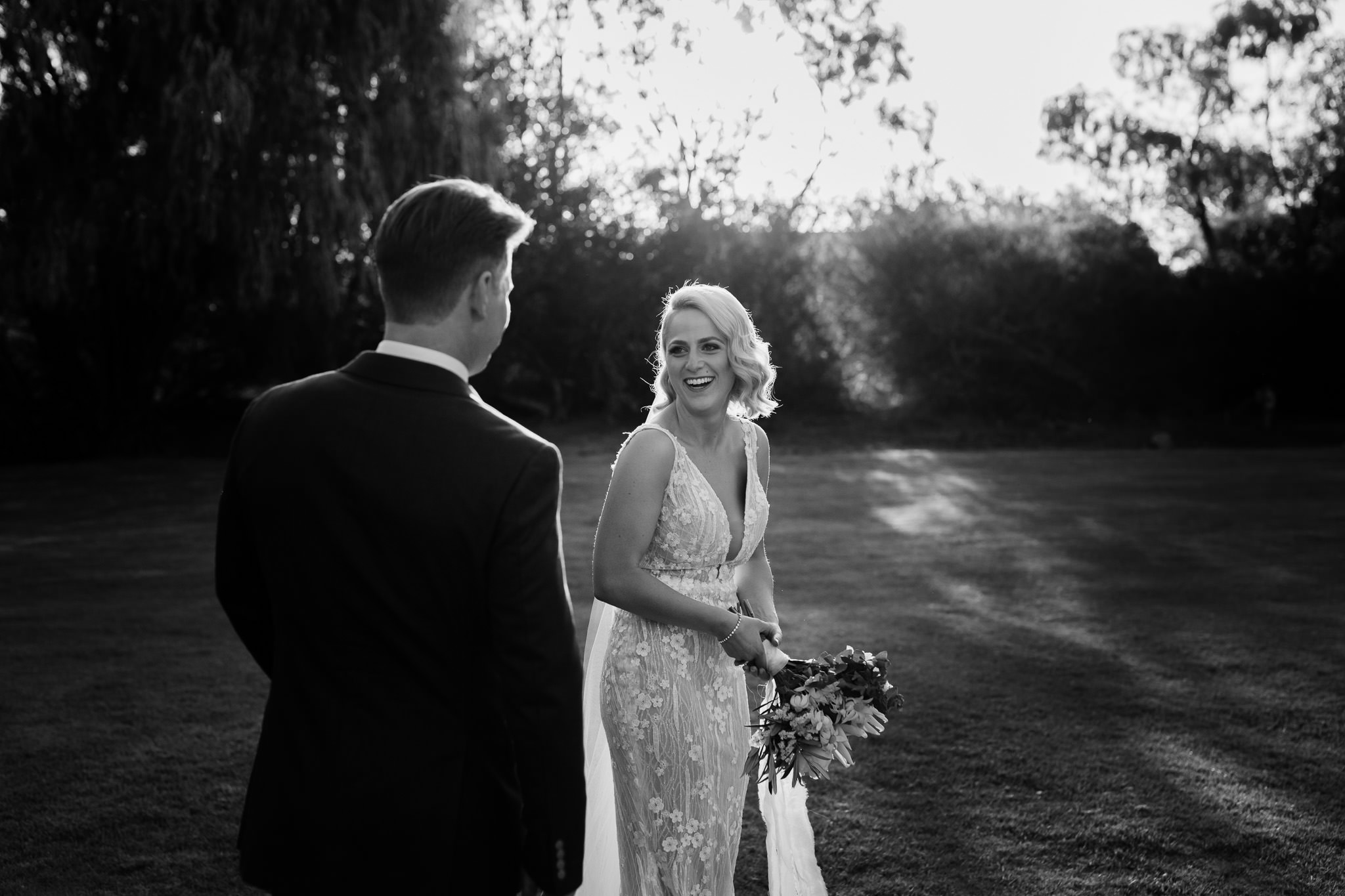 black and white backlit photo of bride in Wedding Societe dress holding native protea bouquet and laughing with her husband with golden light