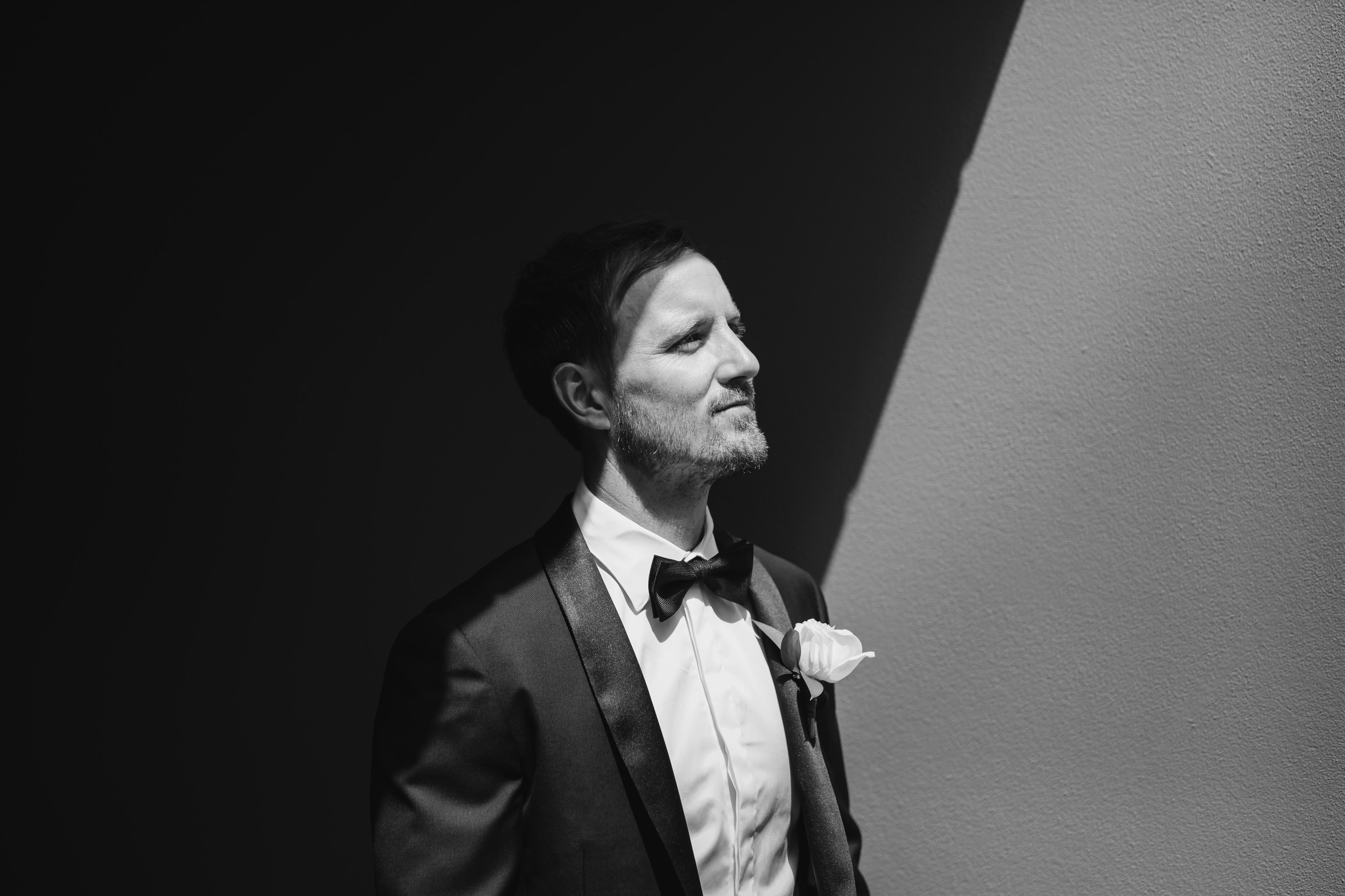 Black and white photo of groom with hard light and shadows