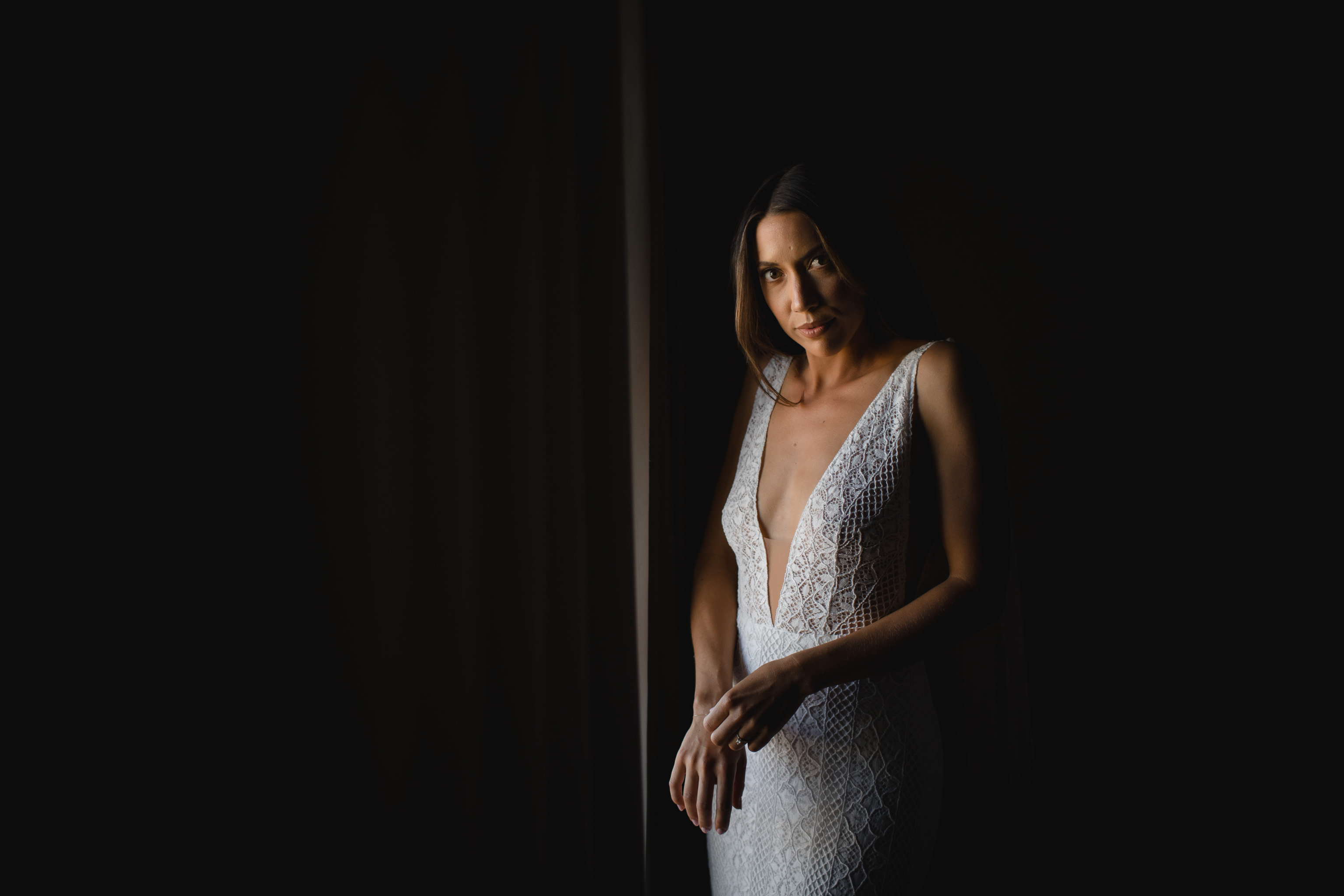 Portrait of bride standing in window light and staring straight at camera