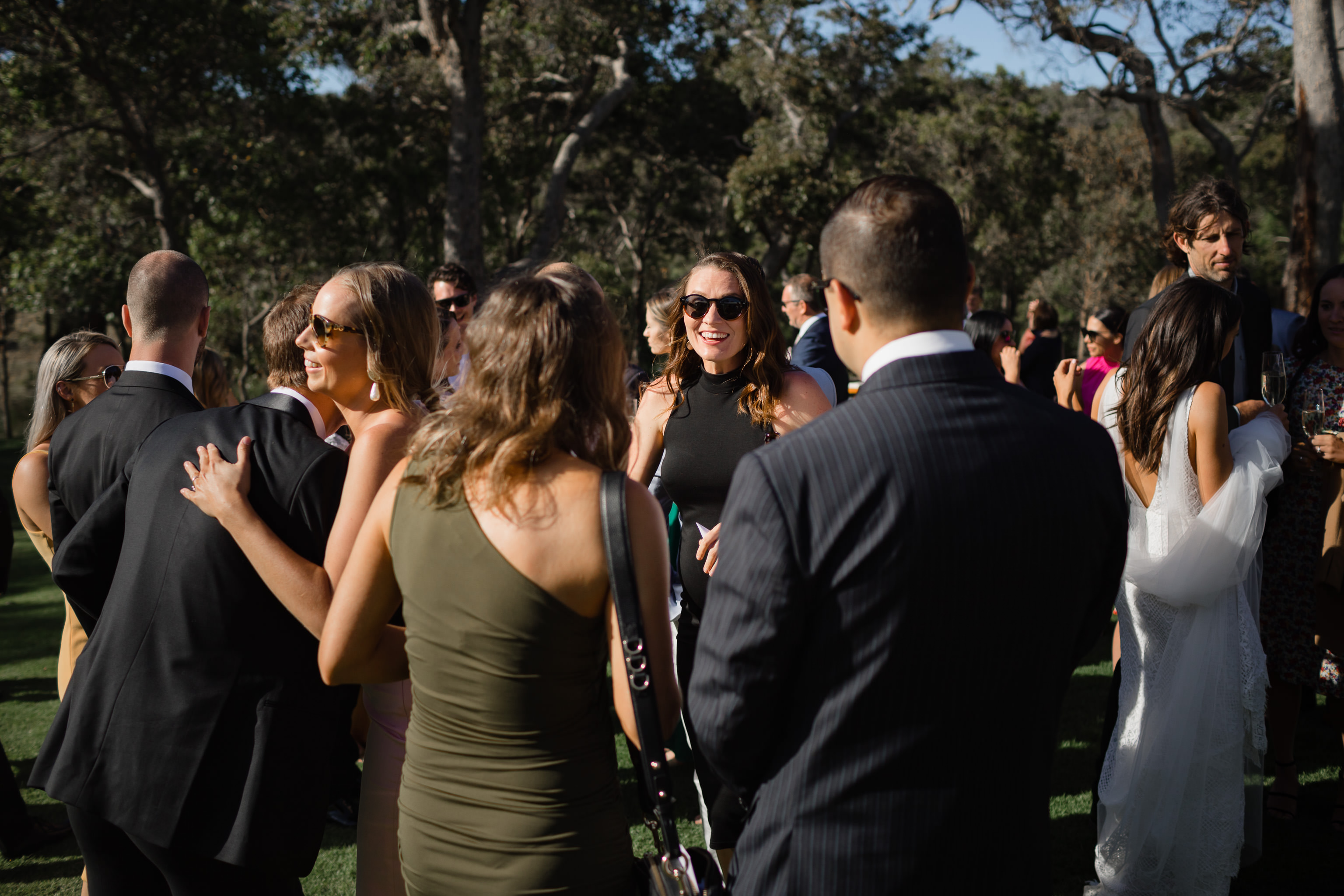 Smiling woman in black sunglasses and black dress at an outdoor wedding at Meelup Farmhouse