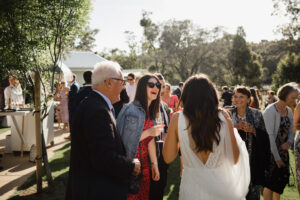 Woman in red dress and denim jacket laughing with bride and group of friends after an outdoor wedding ceremony near Dunsborough