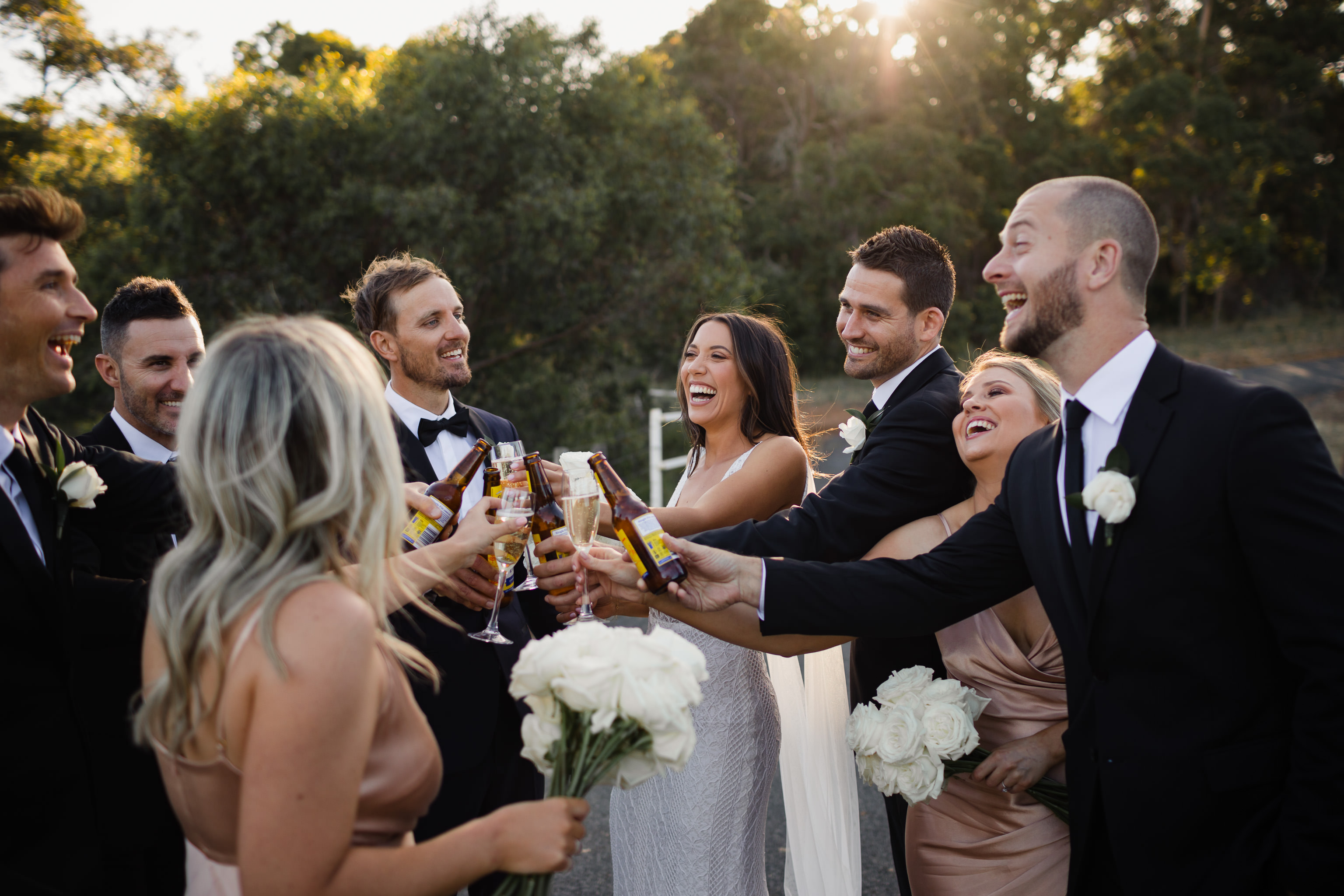 Bridesmaids and groomsmen clinking beers and champagne glasses and enjoying a drink at a wedding at Meelup Farmhouse
