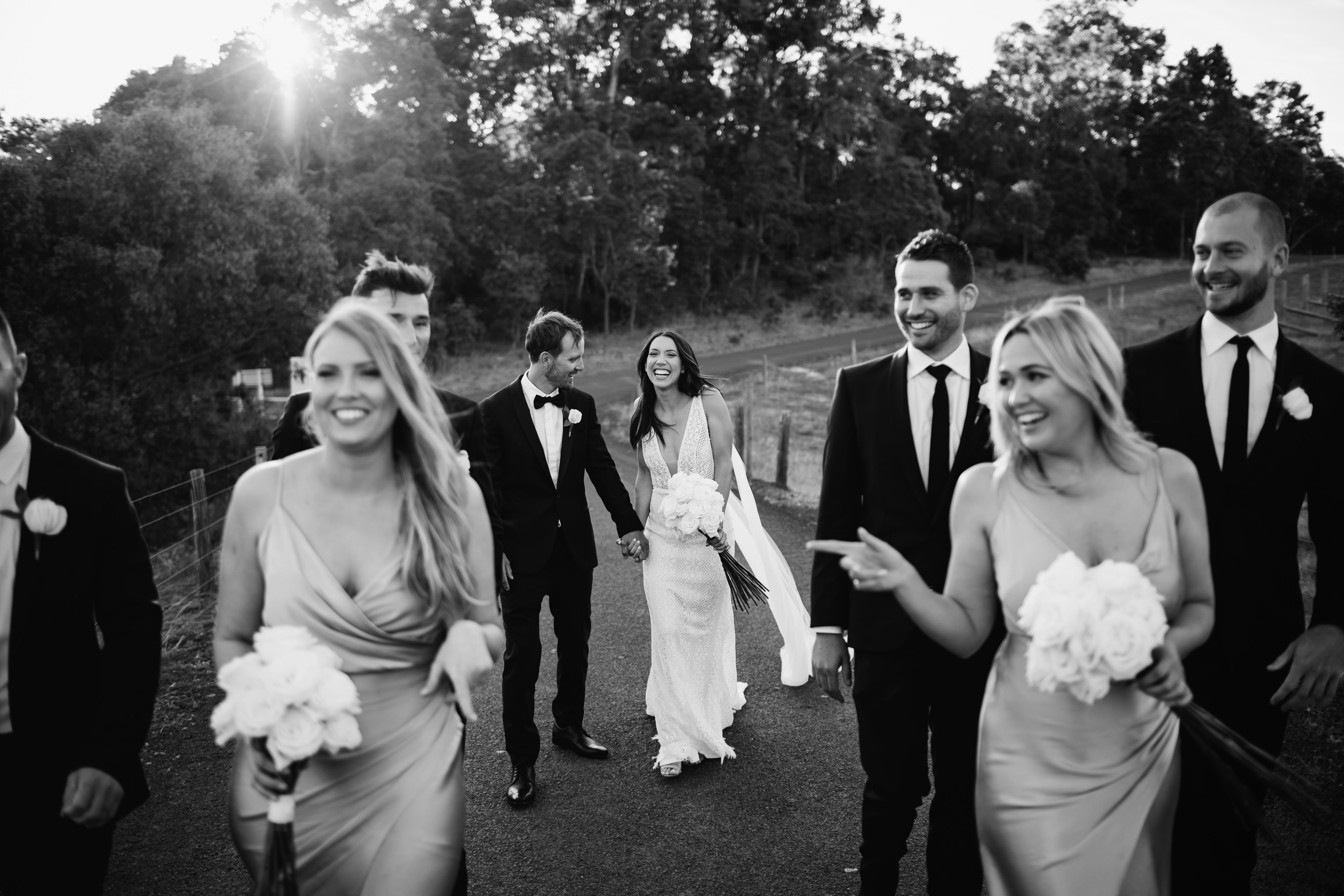 Black and white photo of bride and groom laughing as they walk along a road with Australian bush in the background and bridal party in the foreground