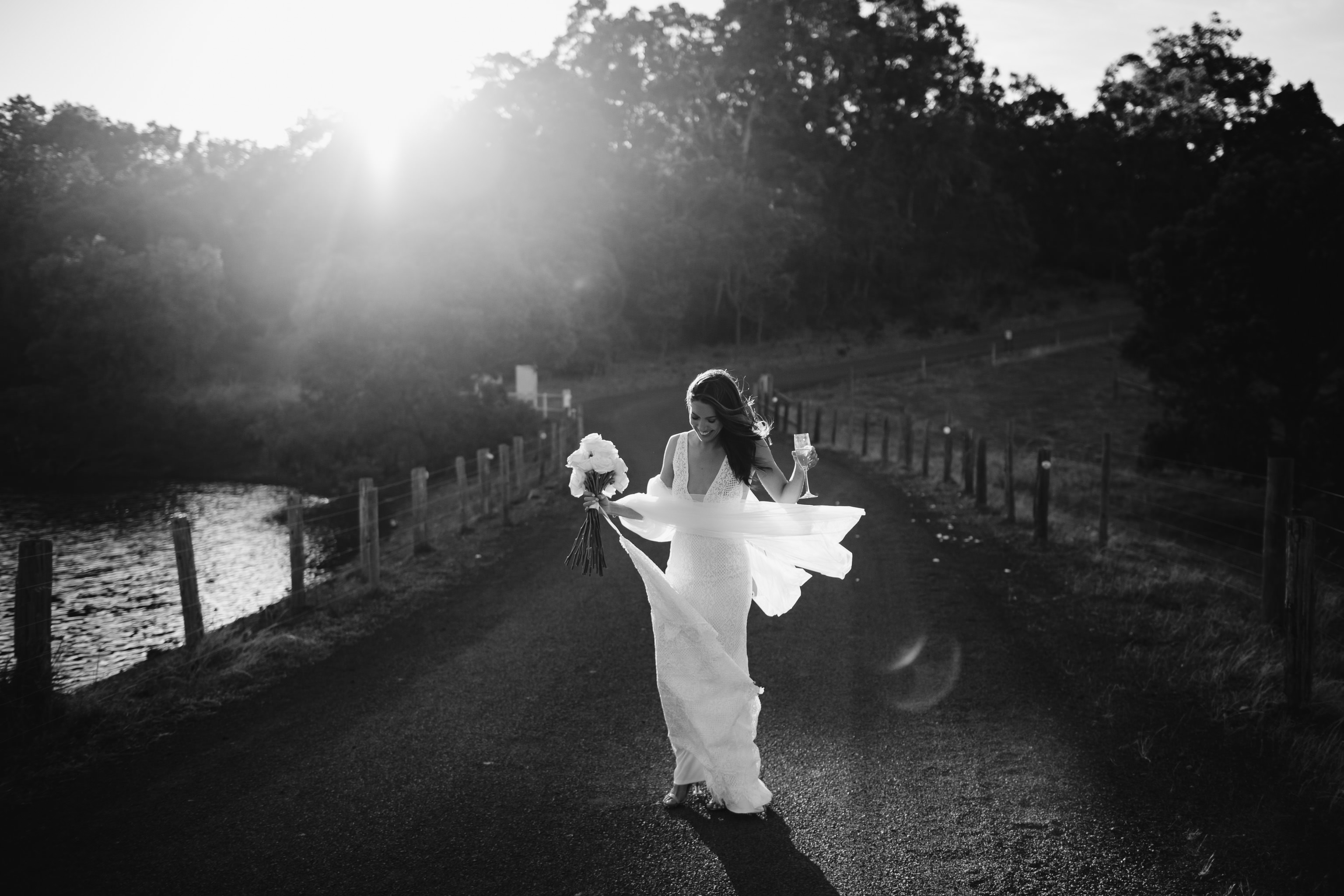 Stunning backlit photo of bride dancing with a glass of champagne while her veil blows in the wind