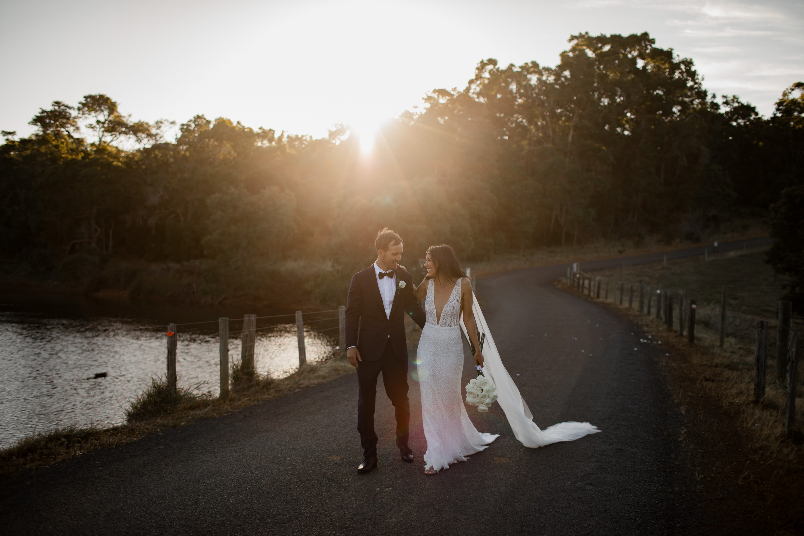 Bride and groom smiling and laughing as they walk down road with golden backlit and a dark background behind them at their wedding at Meelup Farmhouse