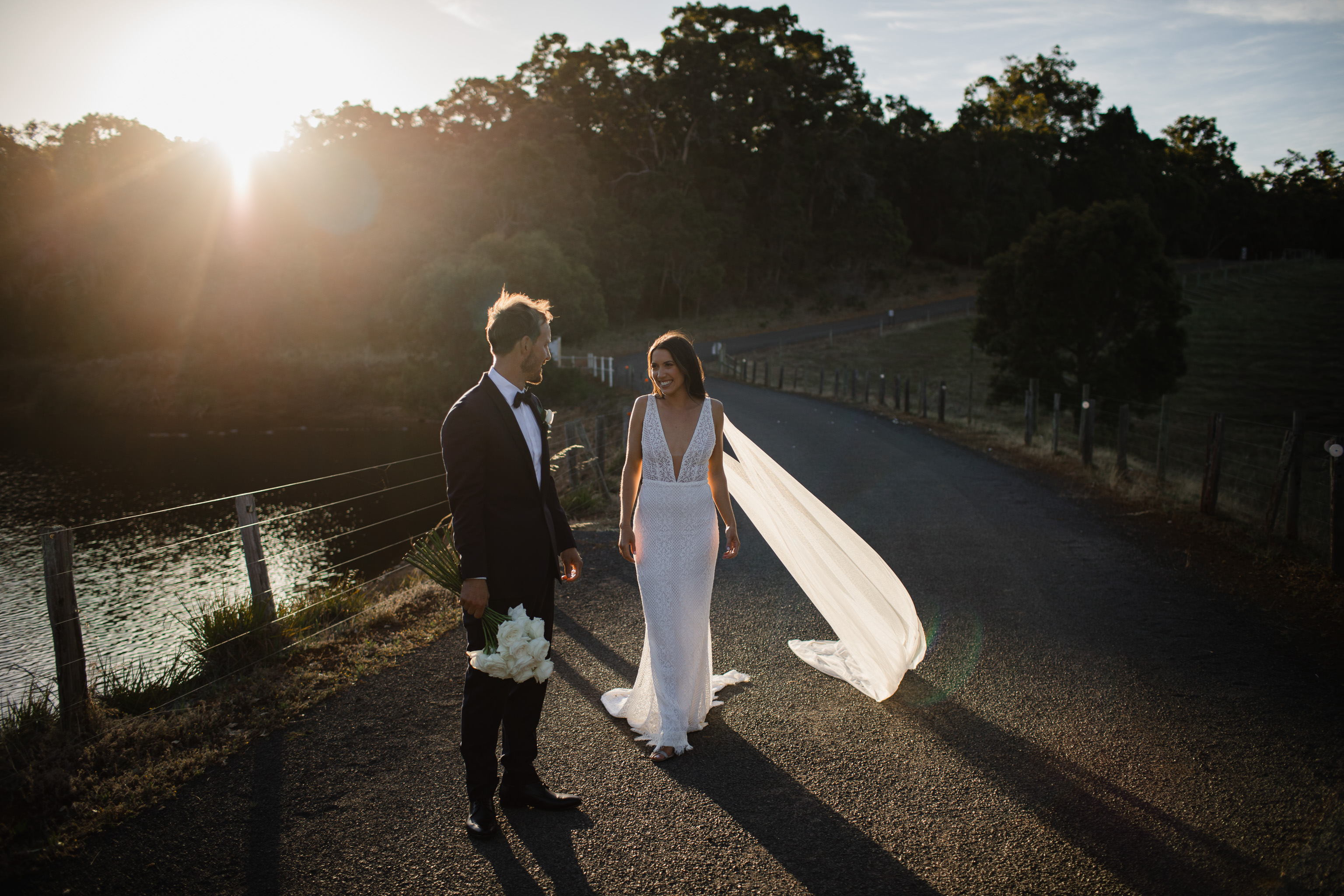 Bride and groom standing in small patch of backlit sunlight against a dark road at sunset at Meelup farmhouse near Eagle Bay