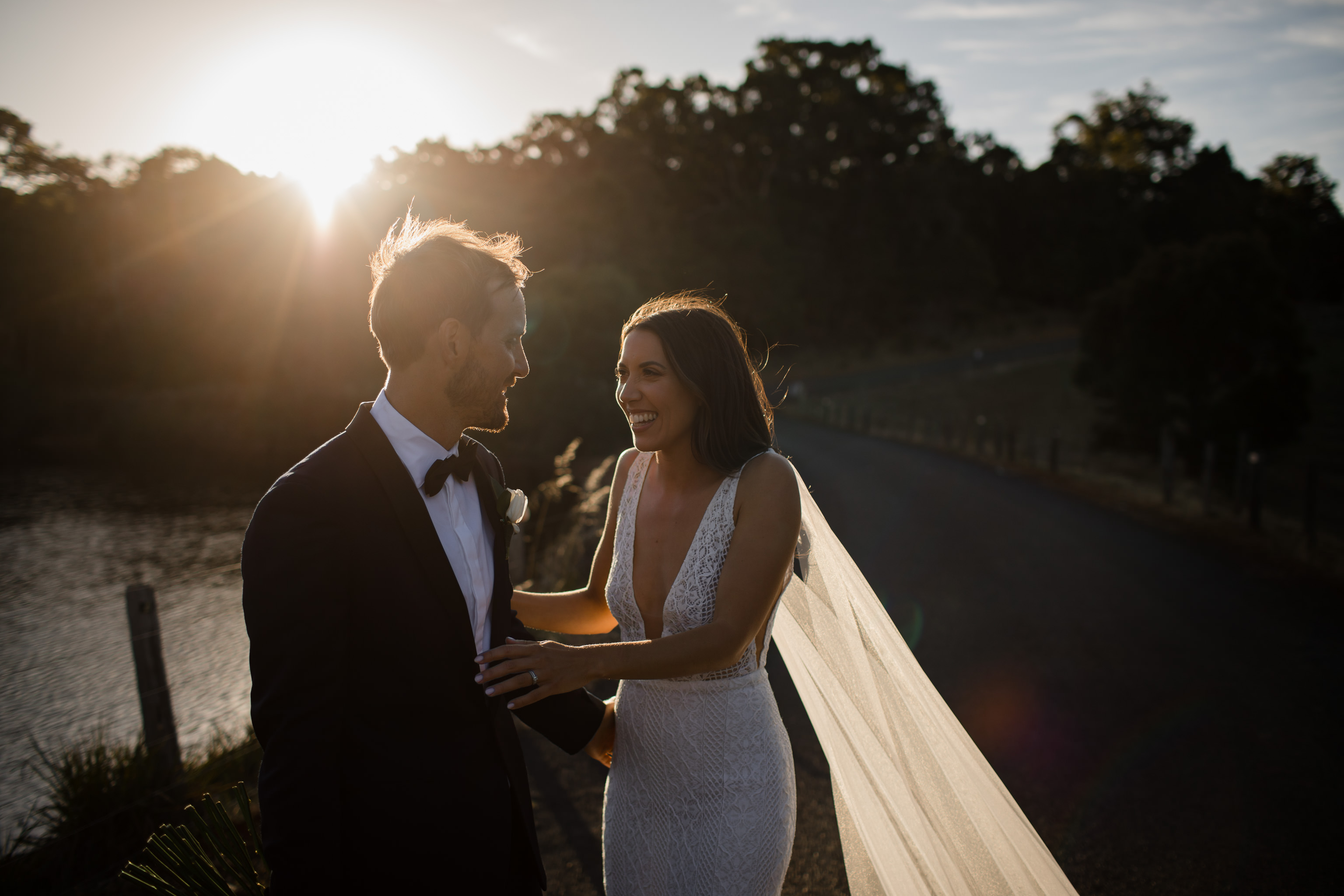 Groom and bride laughing and embracing while her veil blows in the wind and glows in the golden sunset light against a dark background