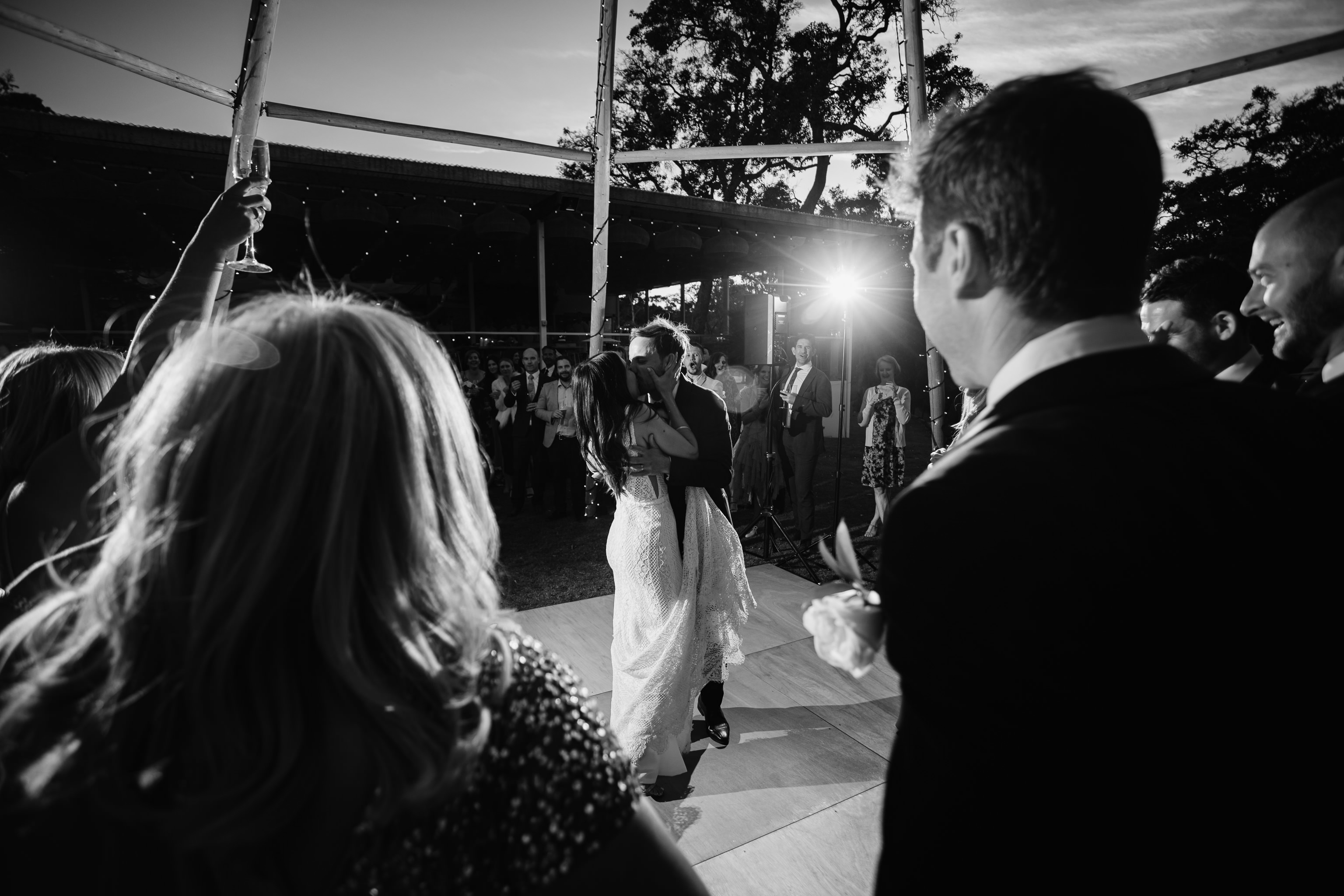 Black and white photo of bride and groom kissing on the dancefloor while their guests look on at Meelup Farmhouse