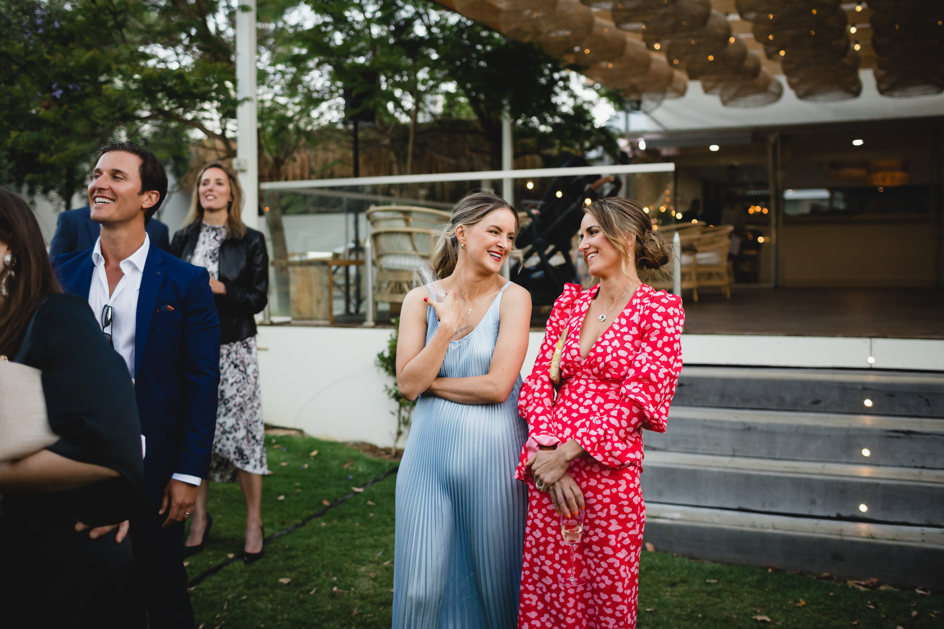 Woman in blue dress laughing with woman in red dress during wedding speeches at Meelup Farmhouse