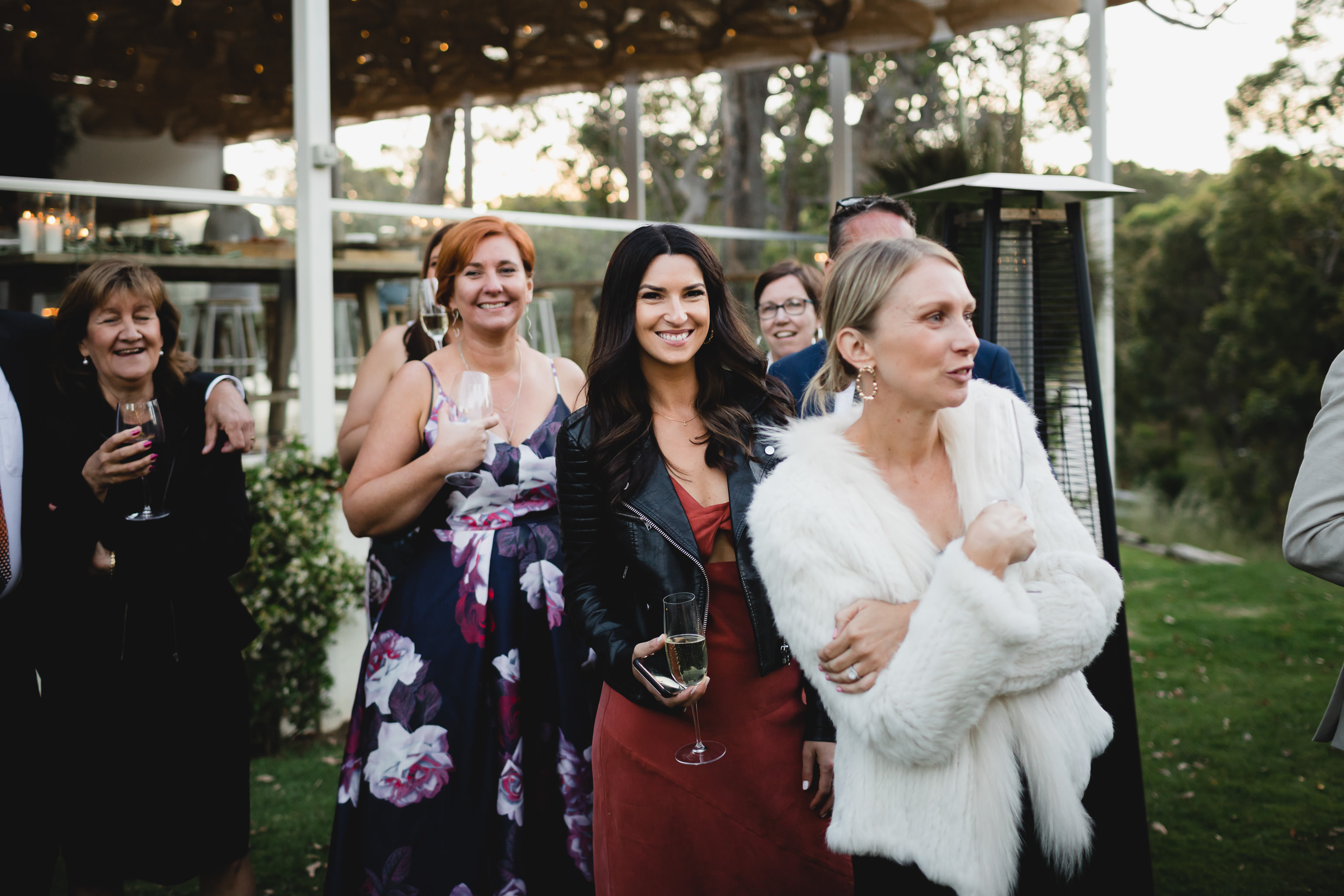 Smiling woman in black leather jacket and orange dress with a glass of champagne at a wedding at Meelup Farmhouse