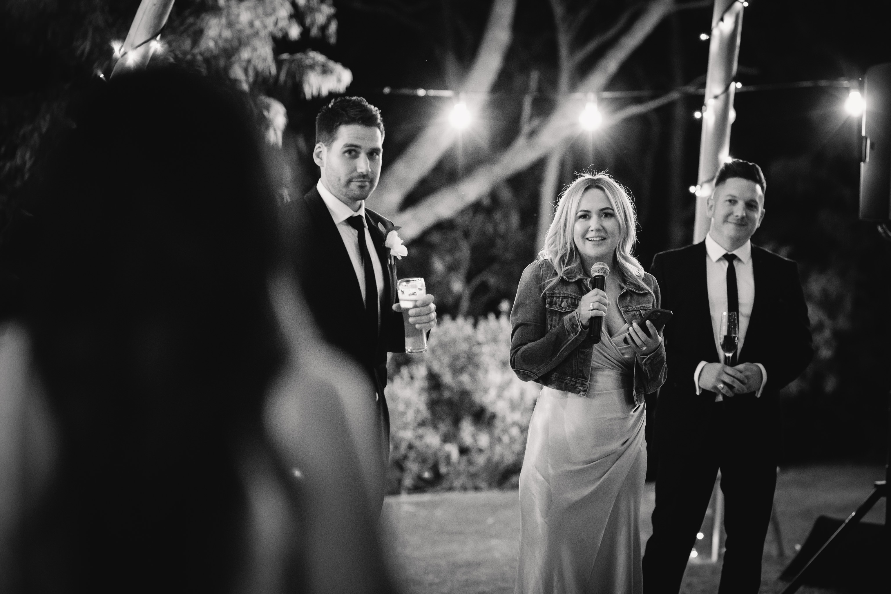 Black and wite photo of bridesmaid looking at bride while she delivers her wedding speech