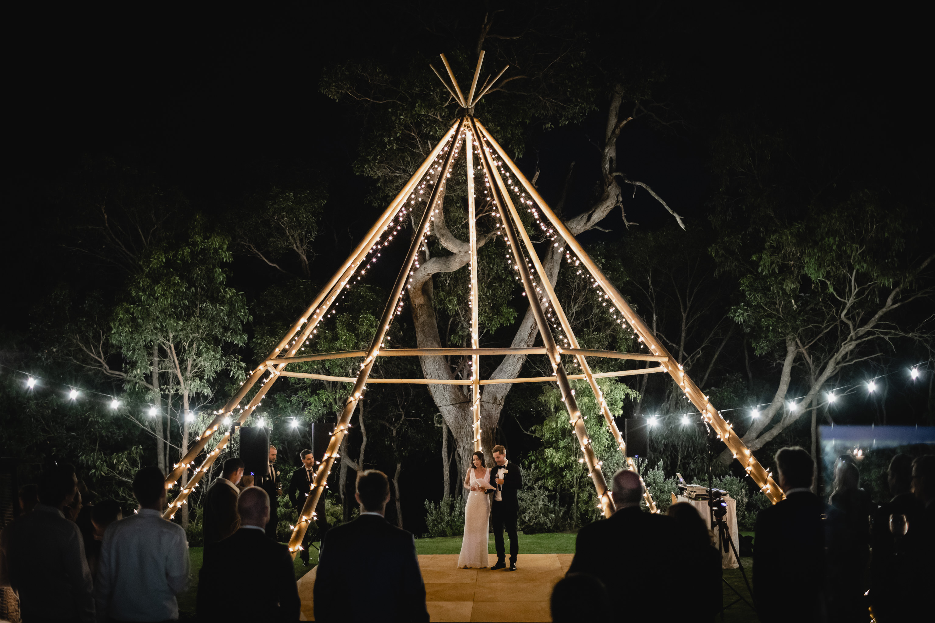 Bride and groom standing under giant tipi covered in festoon lights at their wedding at Meelup Farmhouse