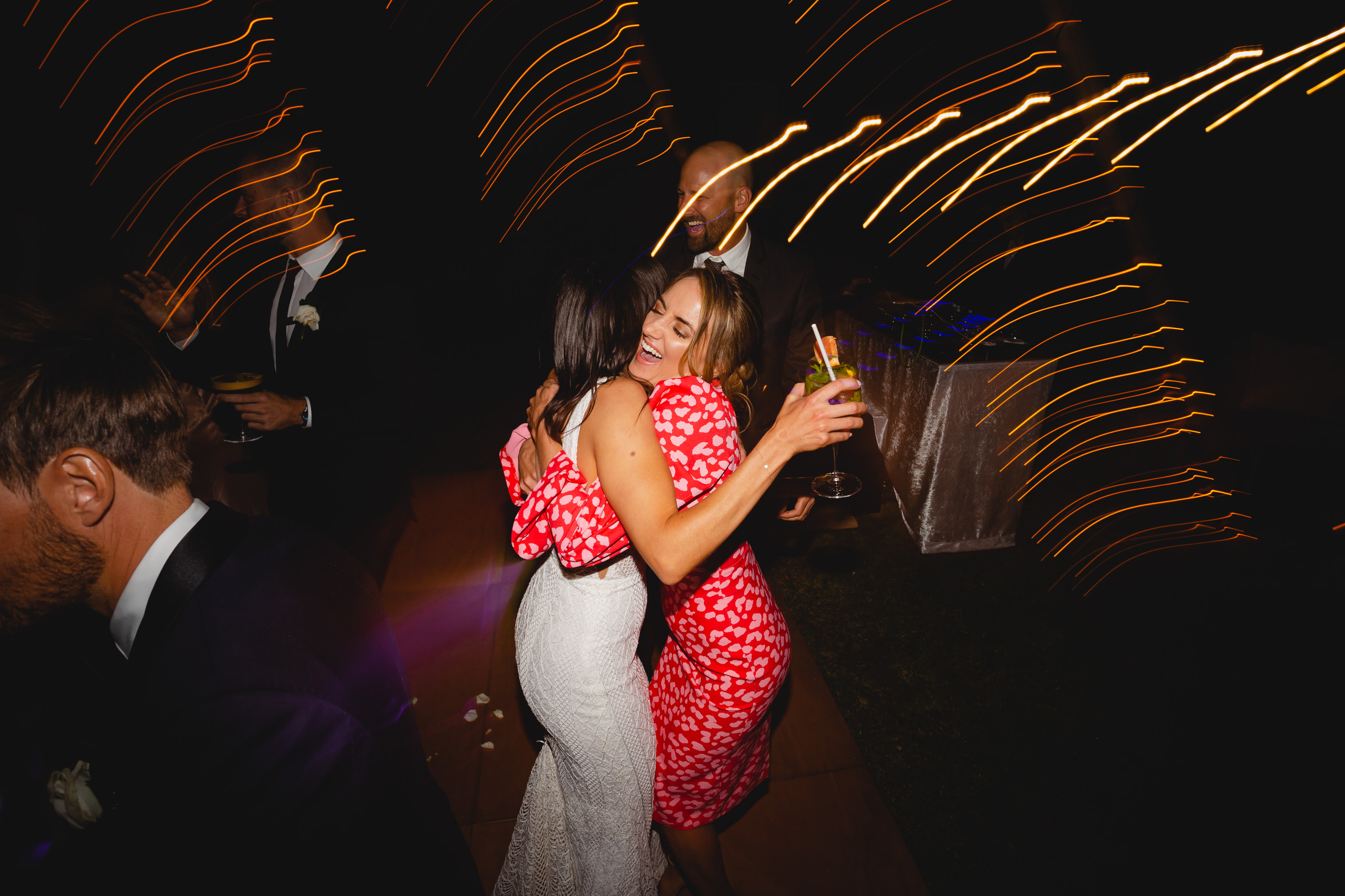 Woman in red dress laughing and hugging bride on dancefloor at wedding reception