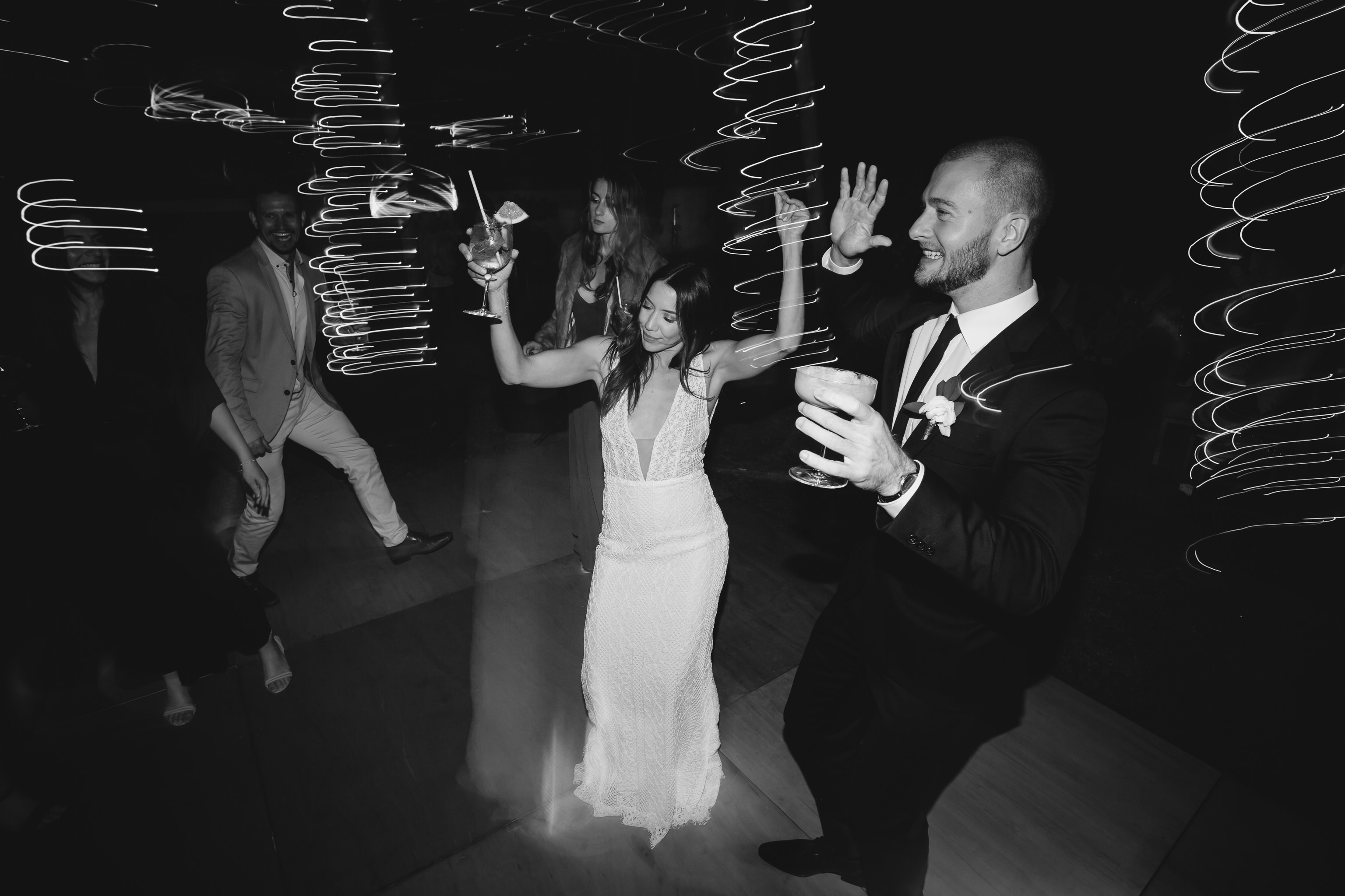 Black and white photo of bride dancing with groomsman with a cocktail in her hand