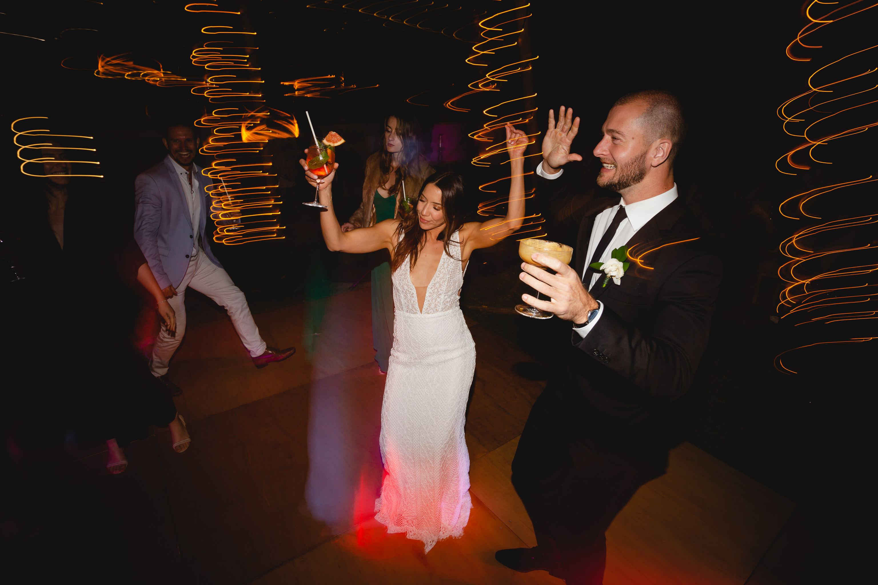 bride dancing with groomsman with a cocktail in her hand