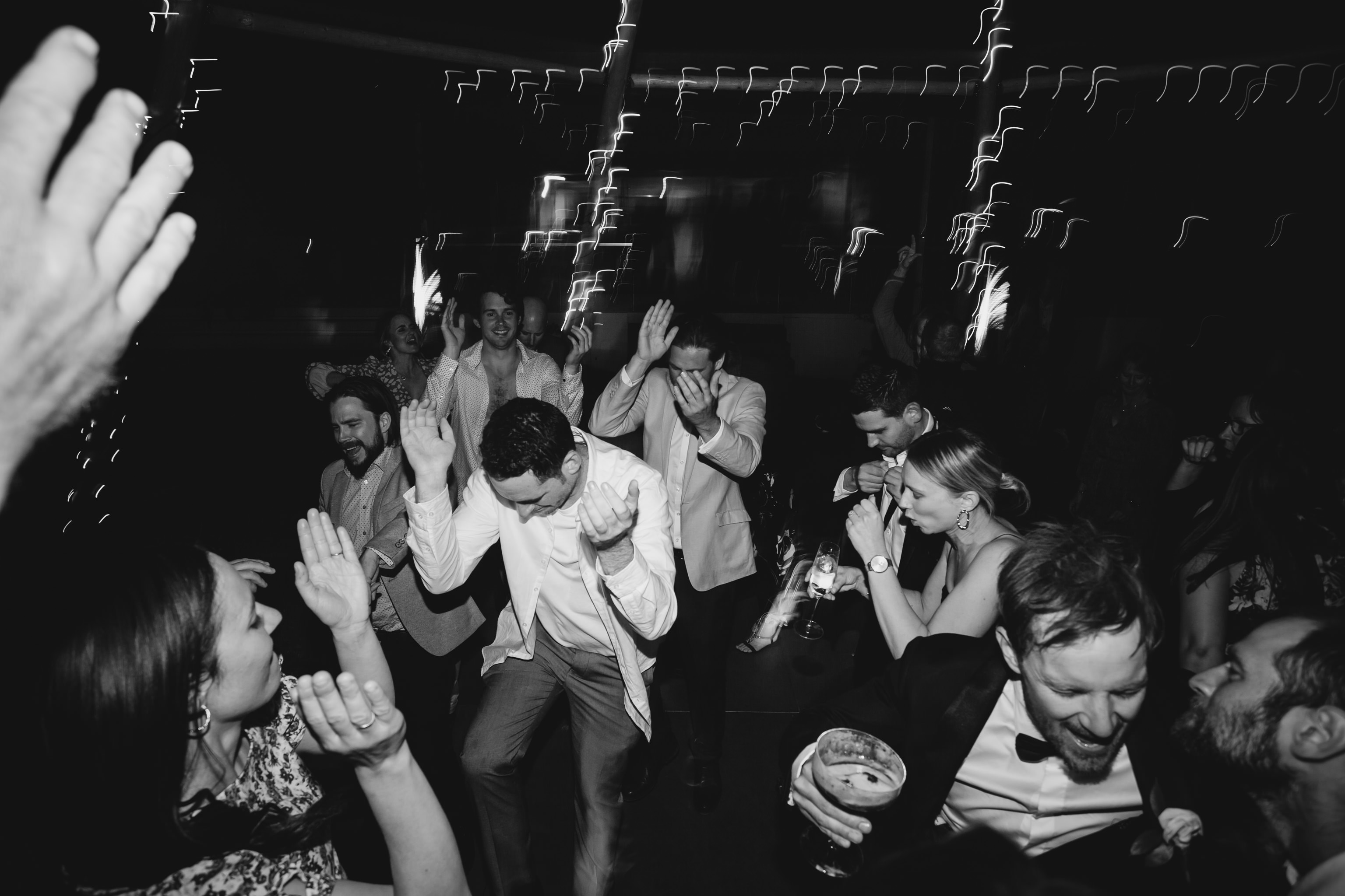 Black and white photo of guests dancing and waving hands and drinks in the air at wedding reception